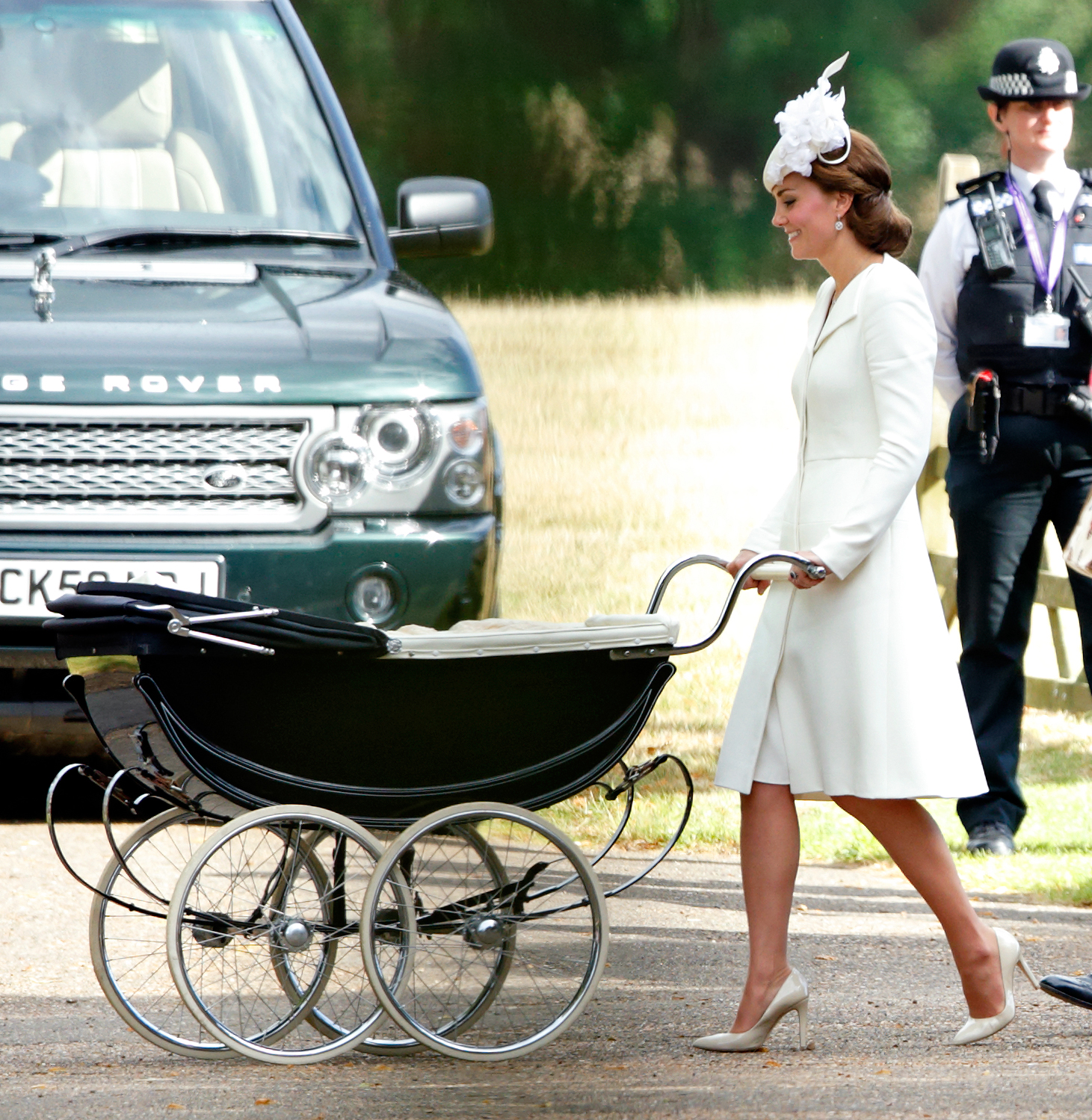KING'S LYNN, UNITED KINGDOM - JULY 05: (EMBARGOED FOR PUBLICATION IN UK NEWSPAPERS UNTIL 48 HOURS AFTER CREATE DATE AND TIME) Catherine, Duchess of Cambridge pushes daughter Princess Charlotte of Cambridge in her pram as she attends the christening of Princess Charlotte of Cambridge at the church of St Mary Magdalene on the Sandringham Estate on July 5, 2015 in King's Lynn, England. (Photo by Max Mumby/Indigo/Getty Images)