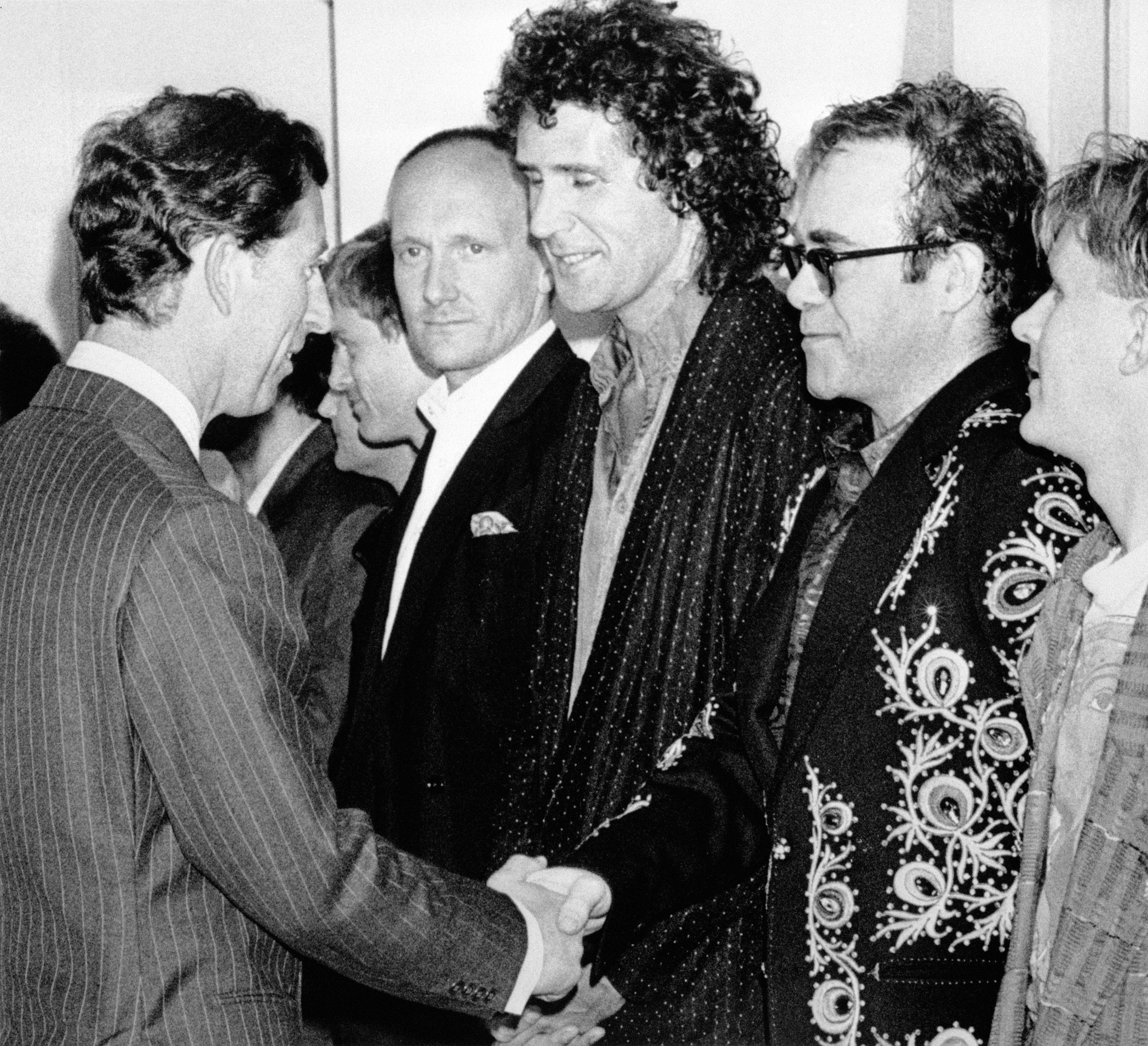 The Prince of Wales shakes hands with Elton John, flanked by his drummer Ray Cooper (l) and Dire Strait's bassist John Illsley (centre) before tonight's rock extravaganza at Wembley to celebrate 10 years of the Prince's Trust.