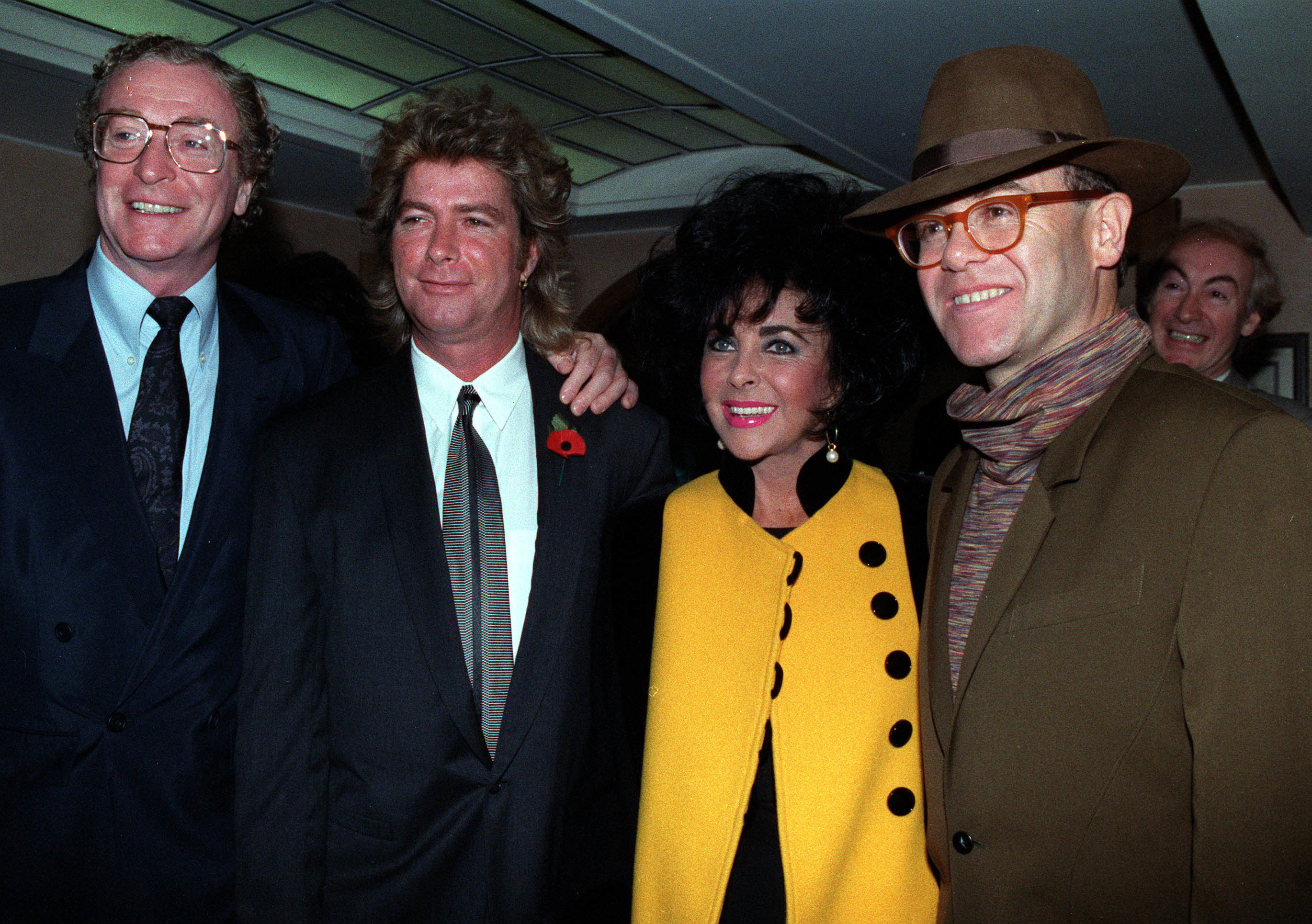 1991: Newly married actress Elizabeth Taylor with her husband, Larry Fortensky (2nd l), actor Michael Caine and pop star Elton John (r) at a charity reopening of the refurbished Mirabelle restaurant in London's Mayfair.