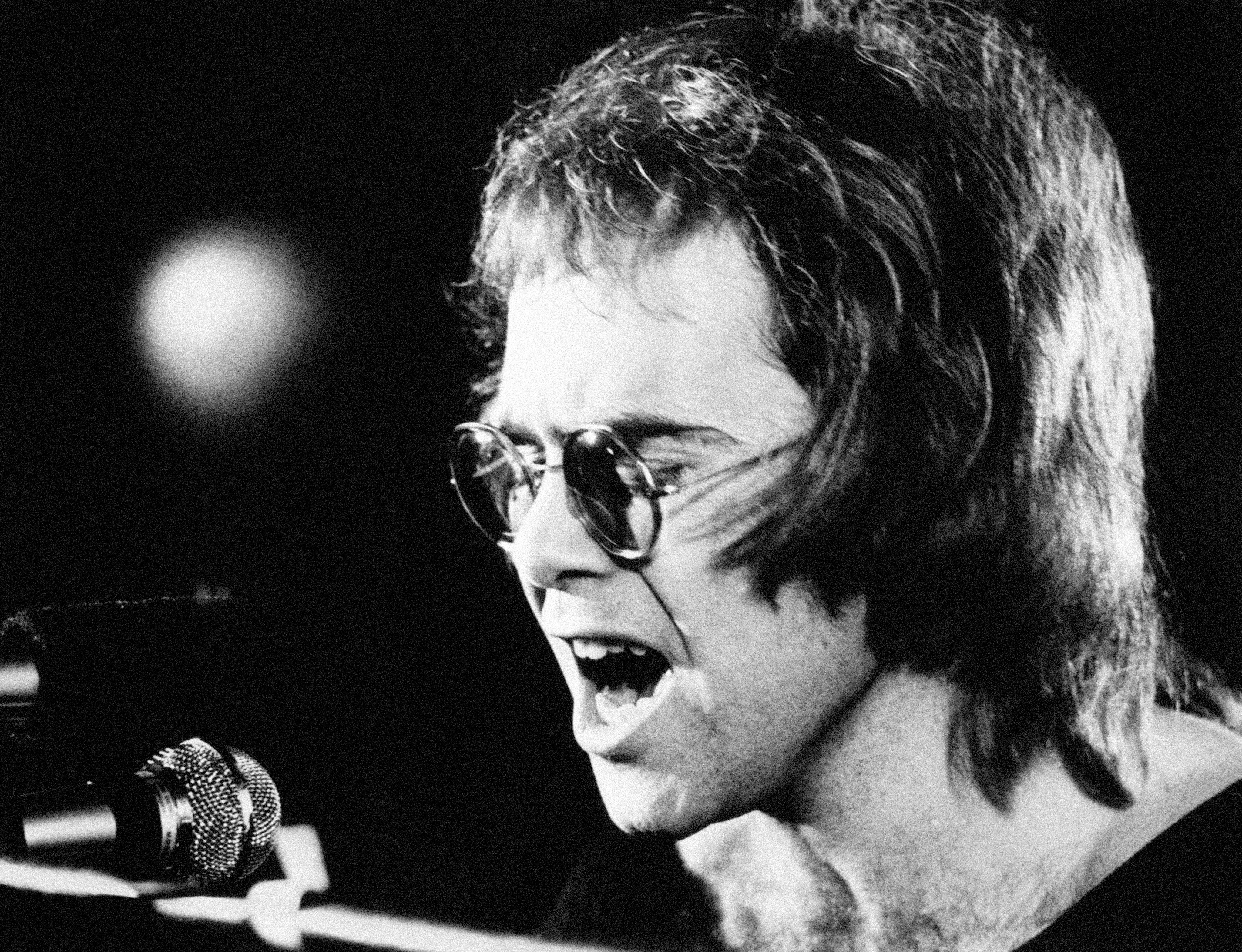Musician Elton John sings in to the microphone on stage during a gig.