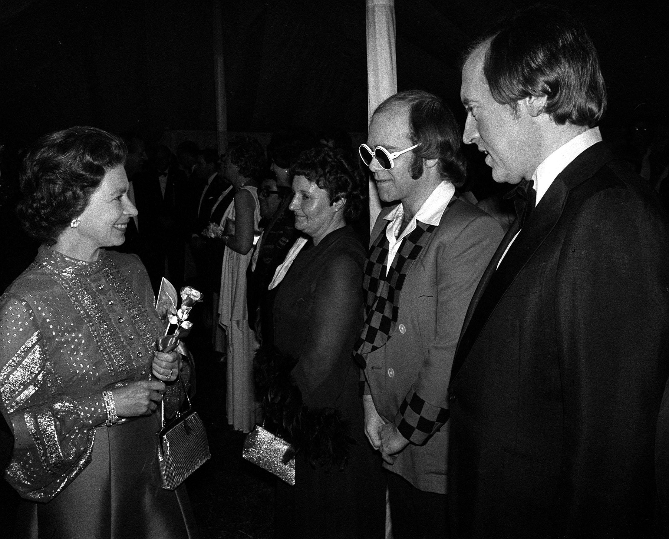 Bespectacled pop star Elton John and television personality David Frost being presented to the Queen at Windsor when they were among a host of stars appearing in a gala variety performance in the Big Top at Home Park in aid of the Queen's Silver Jubilee Appeal.