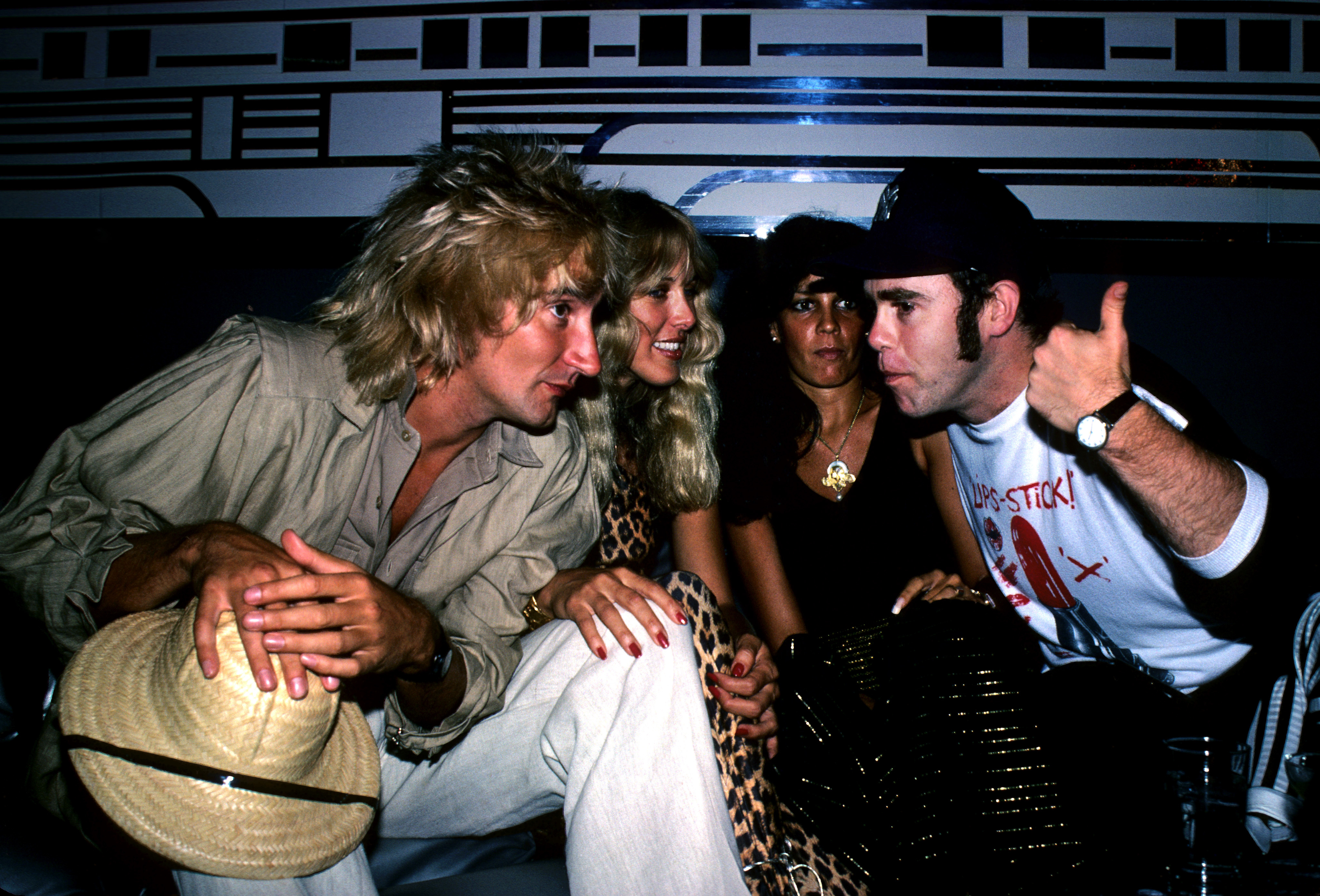 British pop singer Elton John (right), Lana Hamilton (second left), wife of actor George Hamilton, and rock singer Rod Stewart (left) at New York's Studio 54, to celebrate at a party given by RCA Records, who signed John to a contract with the recording company.