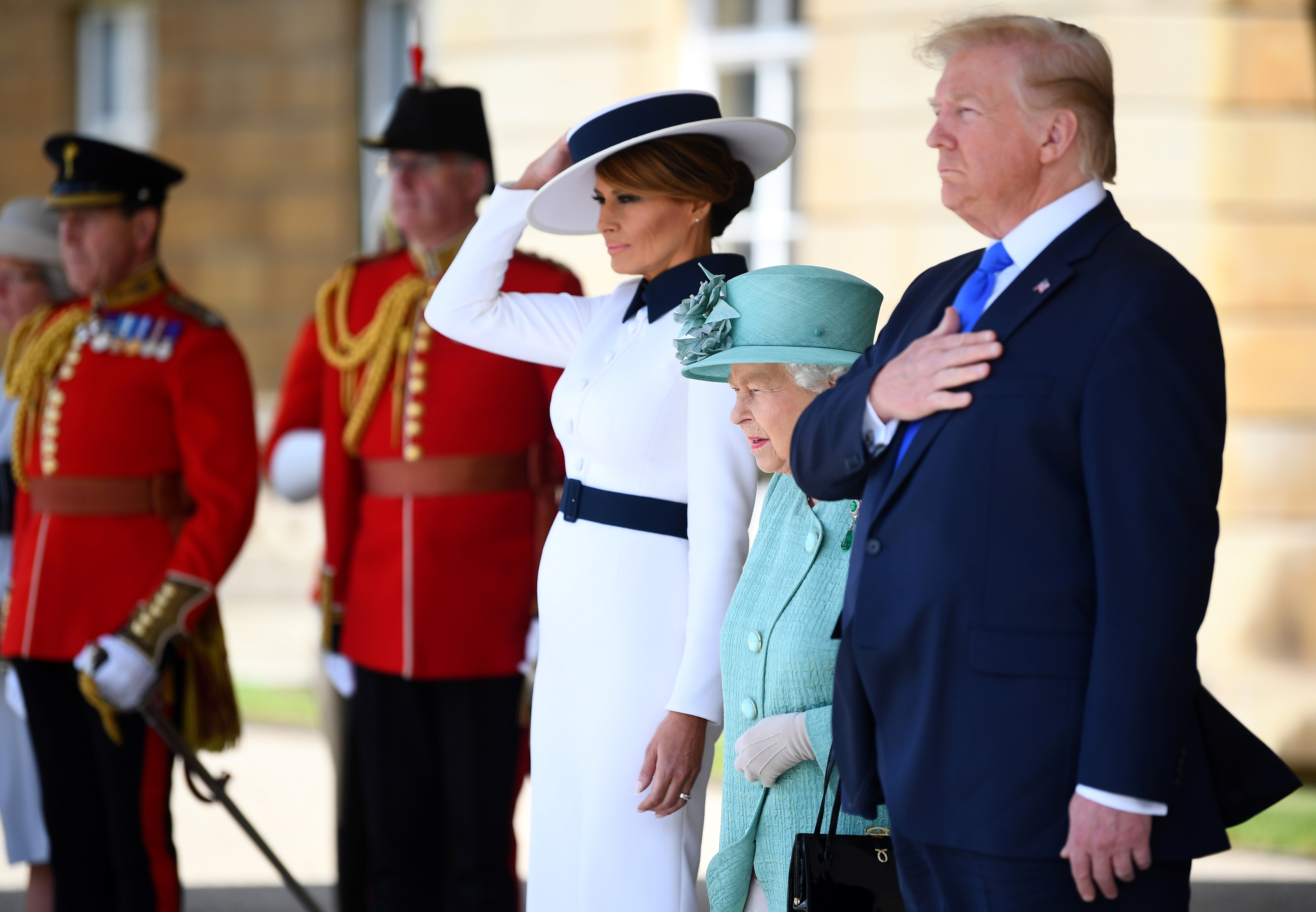 Britain's Queen Elizabeth II (4L) stands with US President Donald Trump (R) and US First Lady Melania Trump (C) as they listen to the US national anthem during a welcome ceremony at Buckingham Palace in central London on June 3, 2019, on the first day of the US president and First Lady's three-day State Visit to the UK. - Britain rolled out the red carpet for US President Donald Trump on June 3 as he arrived in Britain for a state visit already overshadowed by his outspoken remarks on Brexit. (Photo by Victoria Jones / POOL / AFP)        (Photo credit should read VICTORIA JONES/AFP/Getty Images)