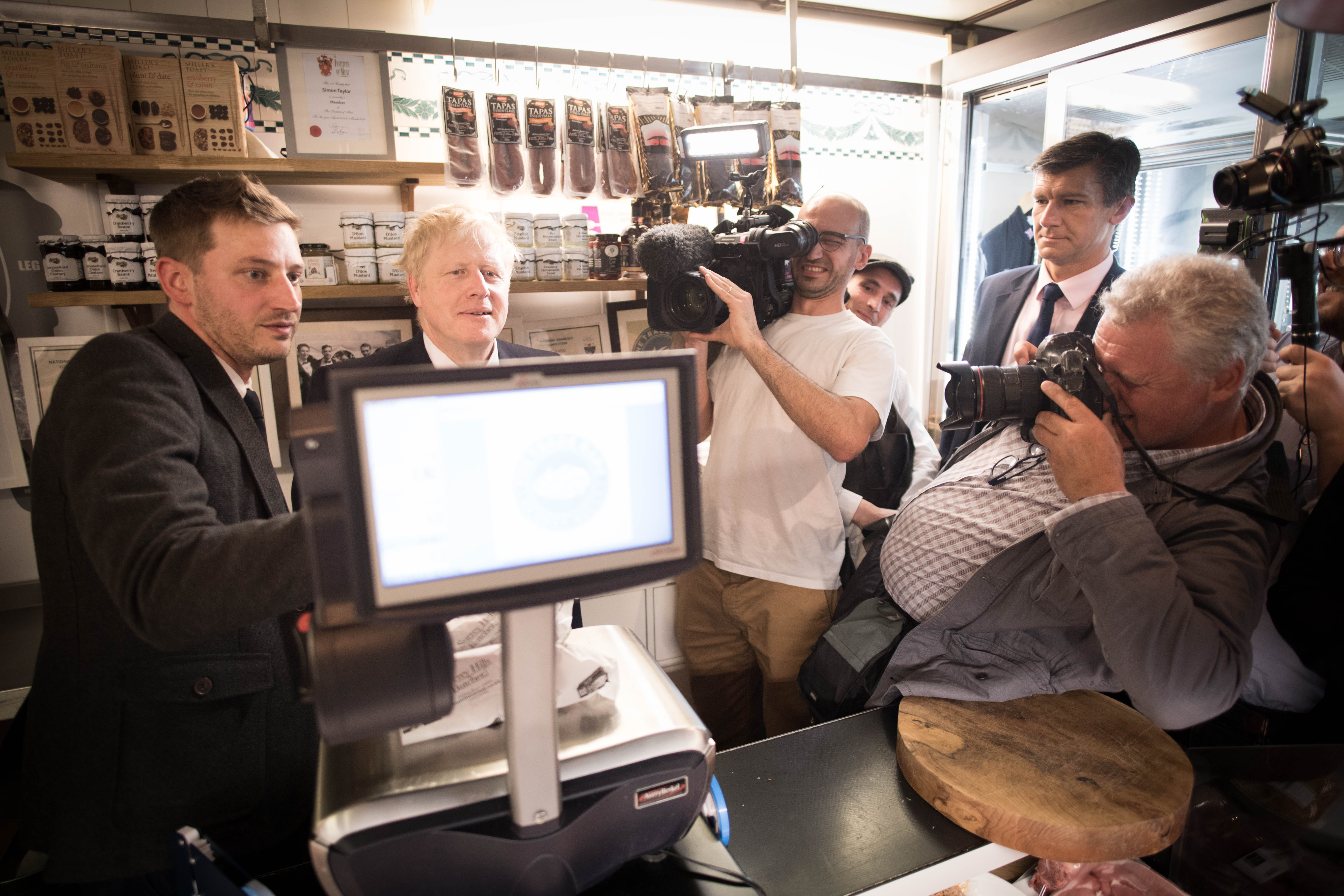 Conservative party leadership candidate Boris Johnson (second left) weighs some produce in the Surrey Hills Butchers in Oxshott, Surrey.