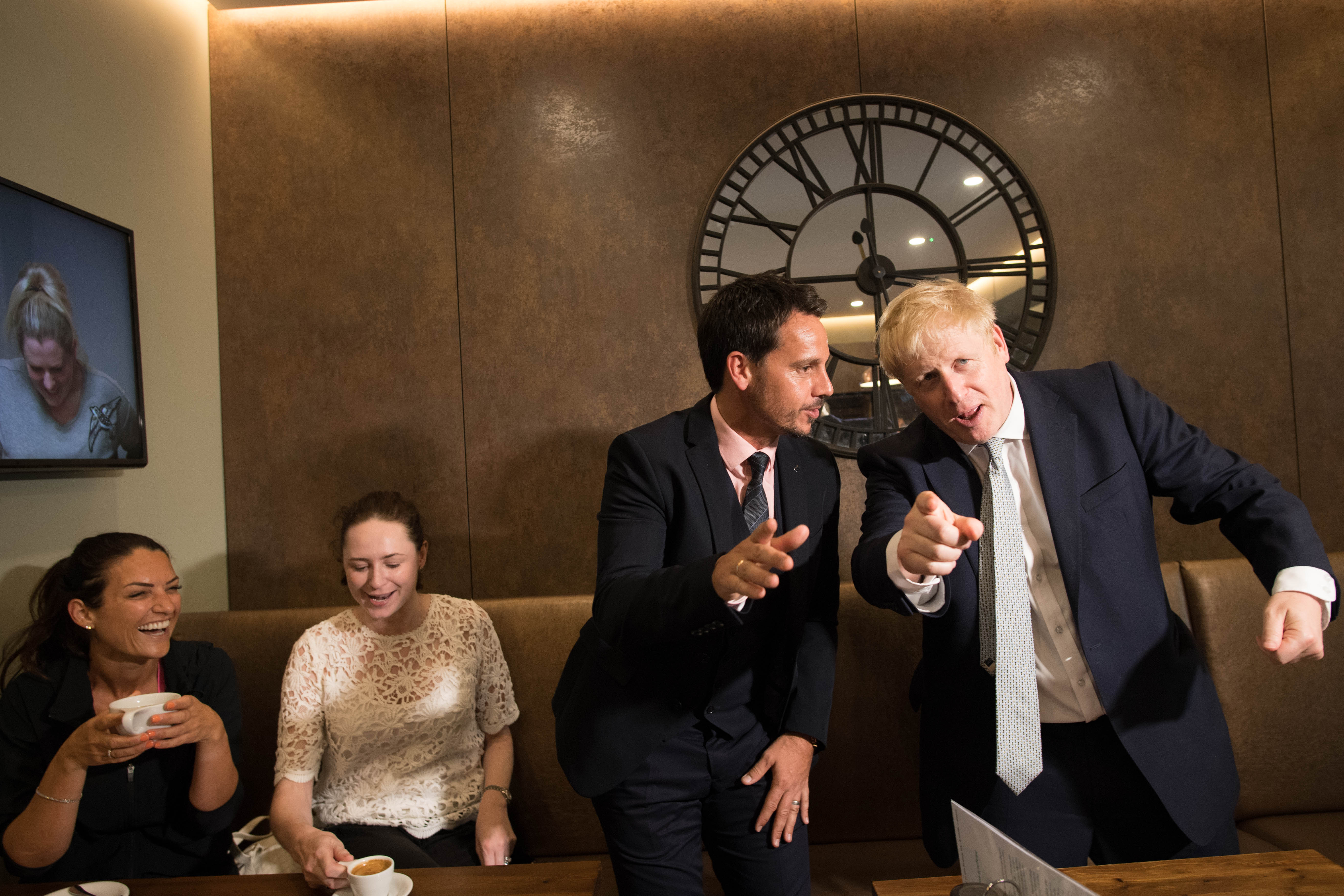 Conservative party leadership candidate Boris Johnson (right) interacts with local business people in the Munch and Wiggles cafe in Oxshott, Surrey.