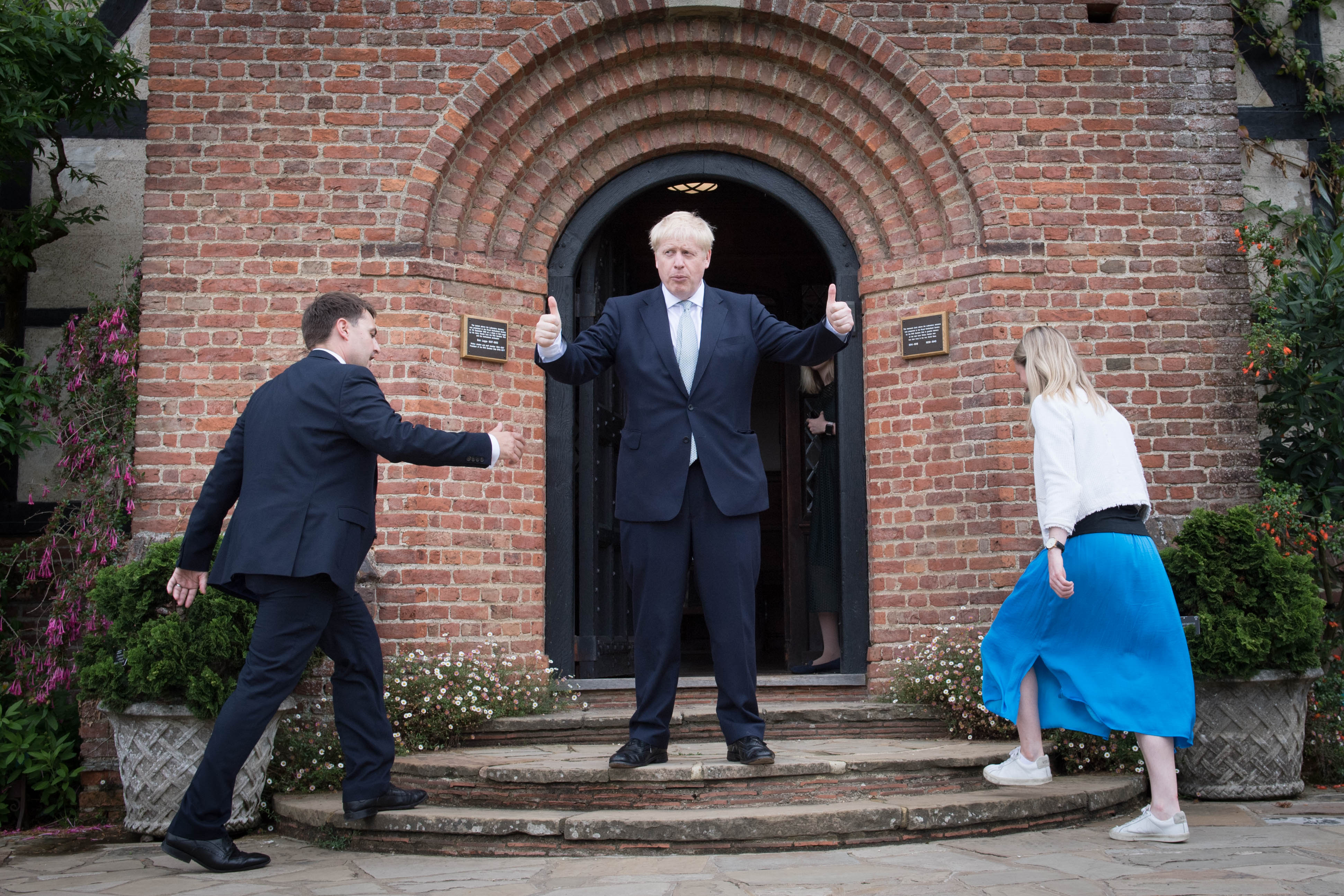 Conservative party leadership candidate Boris Johnson (centre) gestures to visitors as his staff members walk up the steps, during a tour of the RHS (Royal Horticultural Society) garden at Wisley, in Surrey.