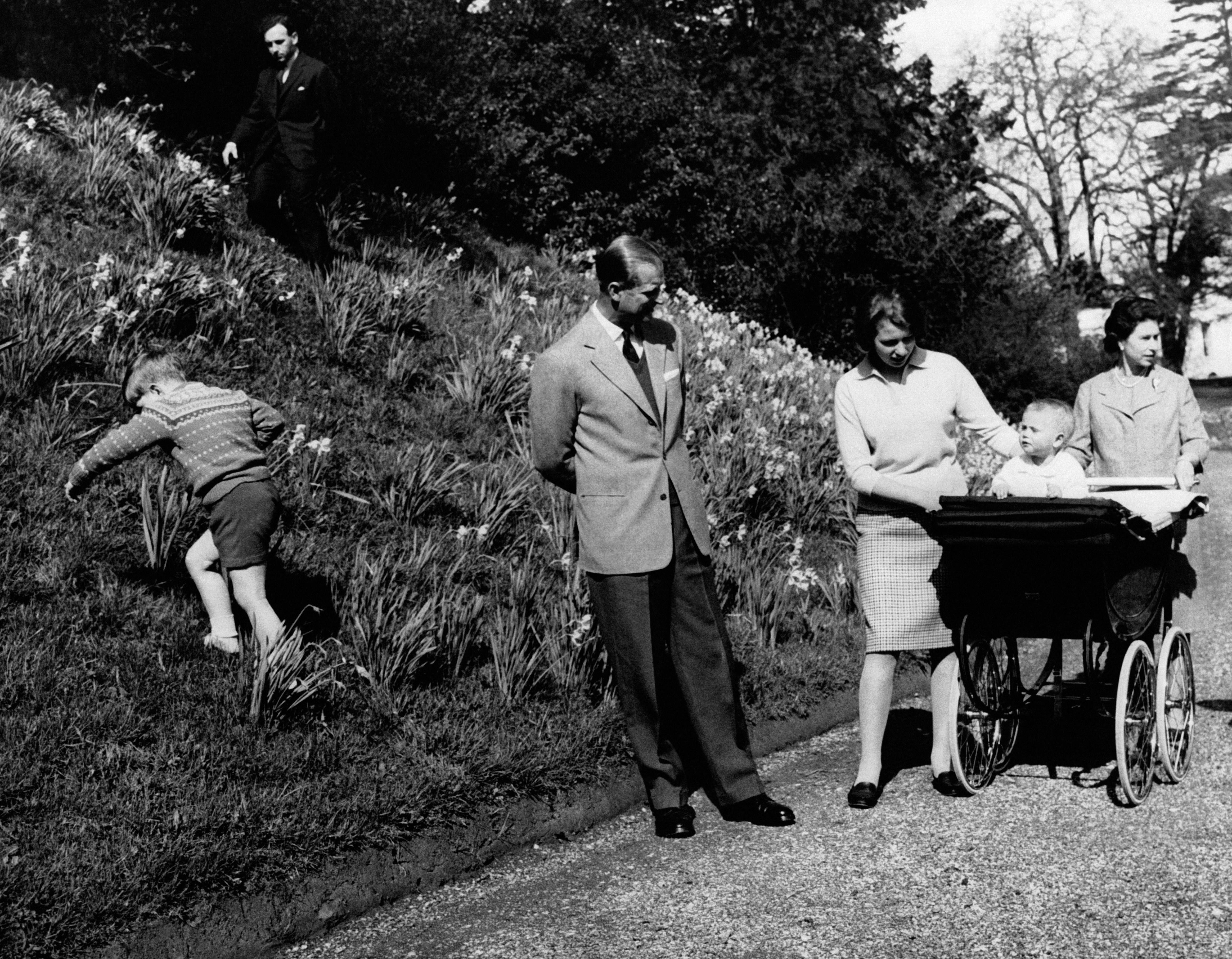 WINDSOR, ROYAUME-UNI - 21 AVRIL: La Reine et la Princesse Anne poussant le landau ou se trouve le petit Prince Edward sous le regard du Duc d Edimbourg, pendant que le Prince Andrew age de 4 ans escalade le monticule dans le jardin de Frogmore House, le 21 avril 1965 a Windsor, Royaume-Uni.  (Photo by Keystone-France\Gamma-Rapho via Getty Images)