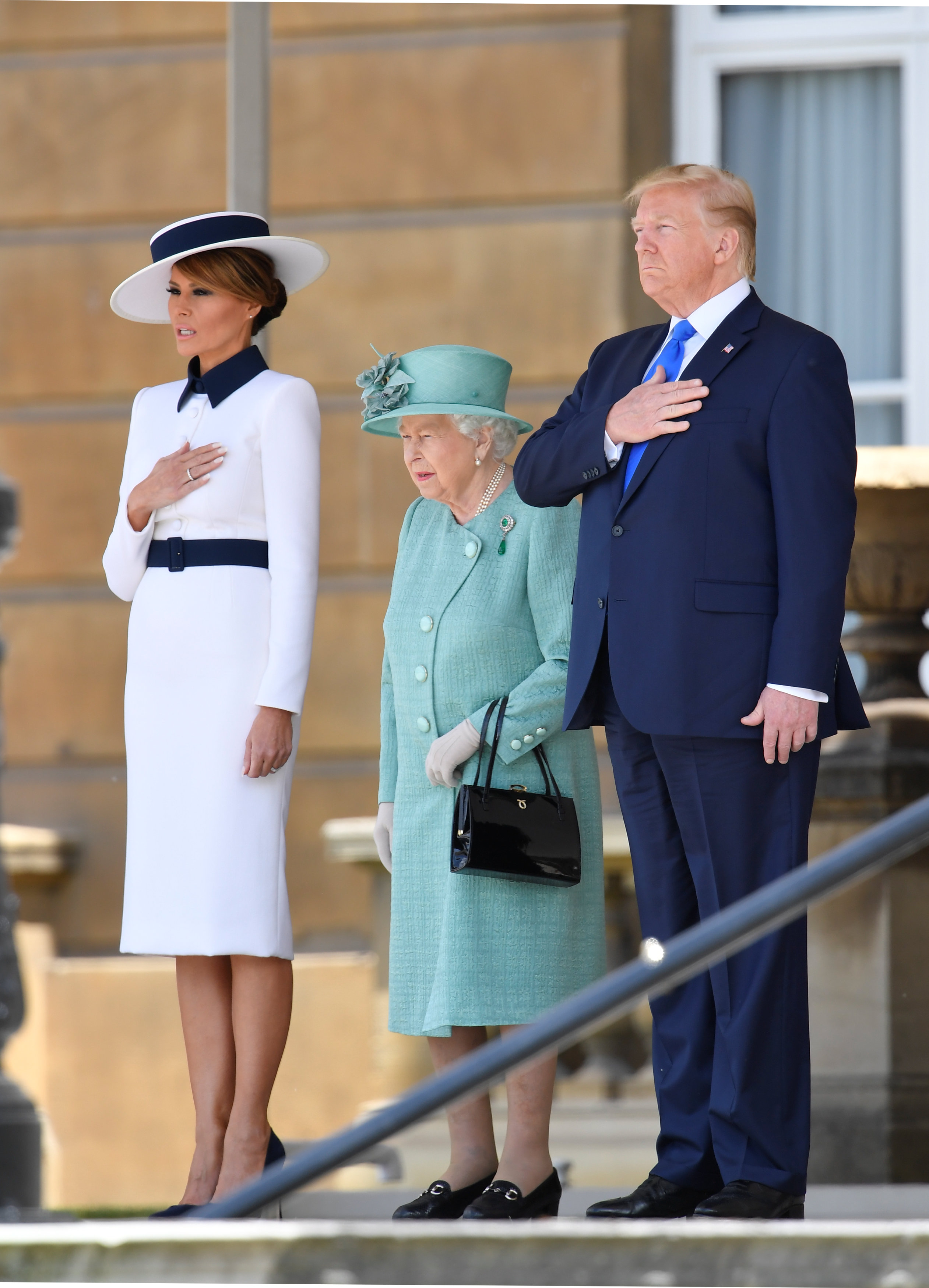 Britain's Queen Elizabeth II (C) stands with US President Donald Trump (R) and US First Lady Melania Trump (L) as they listen to the US national anthem during a welcome ceremony at Buckingham Palace in central London on June 3, 2019, on the first day of the US president and First Lady's three-day State Visit to the UK. - Britain rolled out the red carpet for US President Donald Trump on June 3 as he arrived in Britain for a state visit already overshadowed by his outspoken remarks on Brexit. (Photo by TOBY MELVILLE / POOL / AFP)        (Photo credit should read TOBY MELVILLE/AFP/Getty Images)