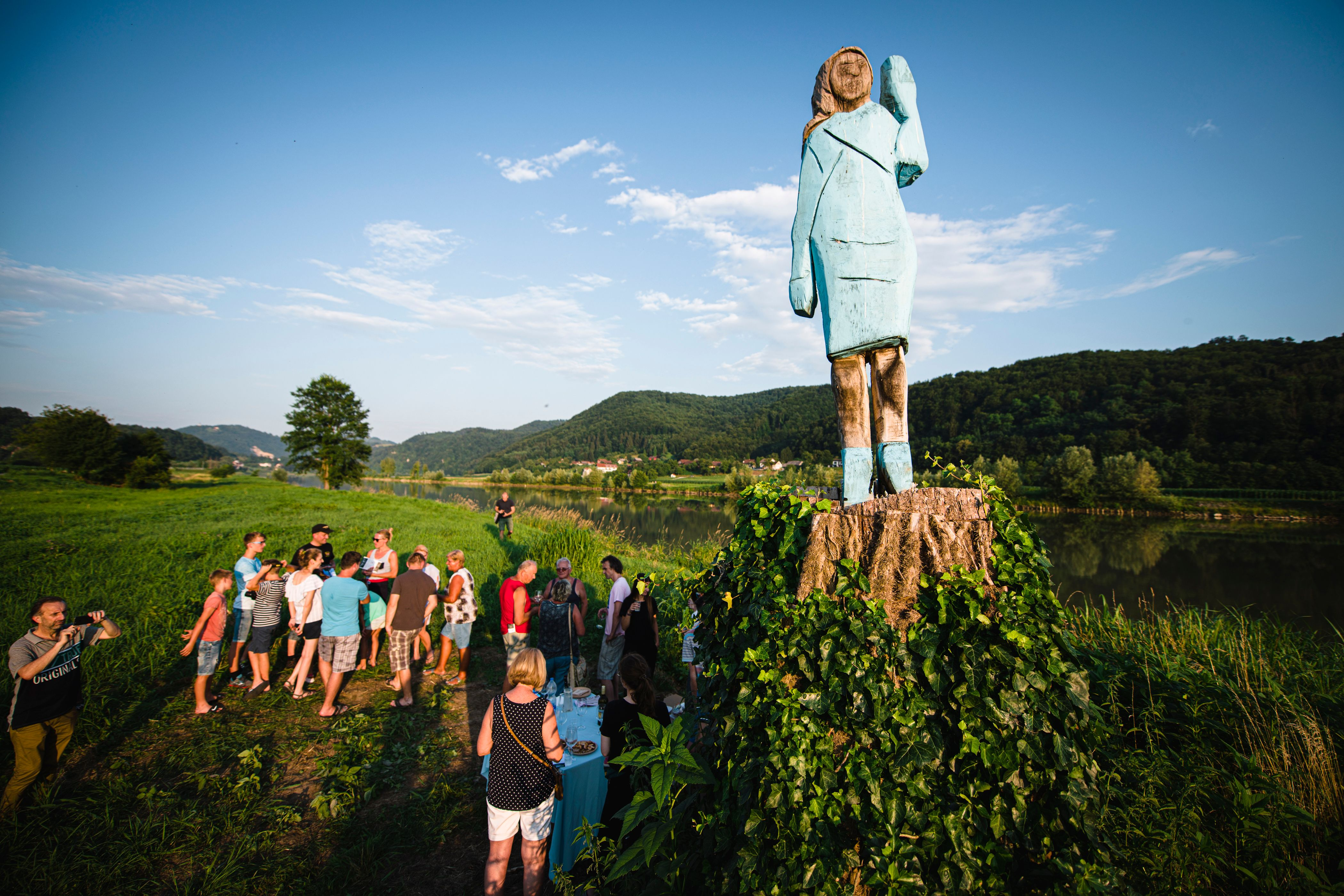 TOPSHOT - People gather around what conceptual artist Ales 'Maxi' Zupevc claims is the first ever monument of Melania Trump, set in the fields near the town of Sevnica, US First Ladys hometown, during a small inauguration celebration on July 5, 2019. - After Melania cake, Melania honey, and even Melania slippers, the Slovenian hometown of the US's first lady will now boast a statue of its most famous daughter -- albeit one which has faced decidedly mixed reviews. The life-size statue on the outskirts of Sevnica was inaugurated on July 5, 2019. (Photo by Jure Makovec / AFP) / RESTRICTED TO EDITORIAL USE - MANDATORY MENTION OF THE ARTIST UPON PUBLICATION - TO ILLUSTRATE THE EVENT AS SPECIFIED IN THE CAPTION        (Photo credit should read JURE MAKOVEC/AFP/Getty Images)