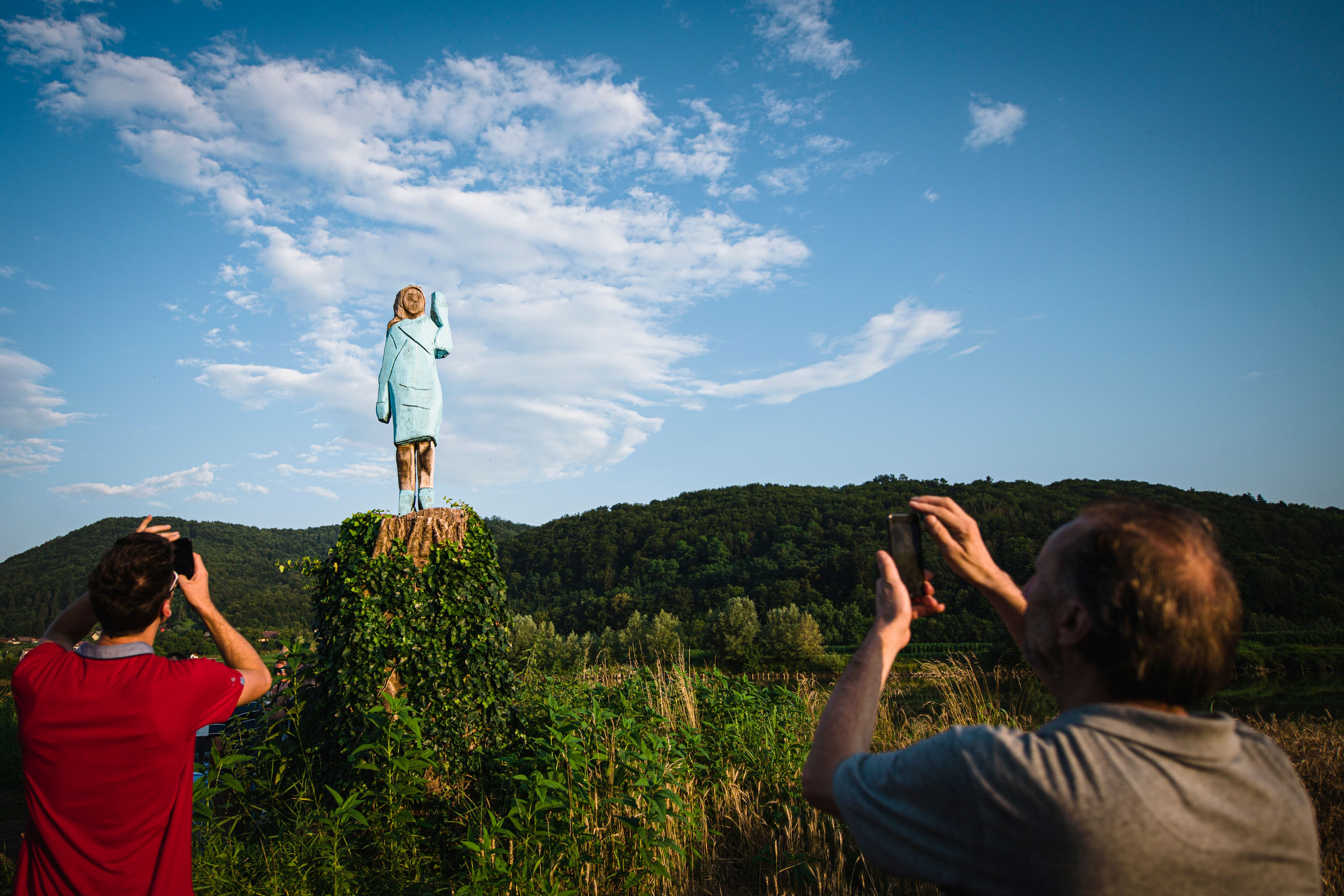 People take pictures of sculpture by conceptual artist Ales 'Maxi' Zupevc, who claims is the first ever monument of Melania Trump, set in the fields near town of Sevnica, US First Ladys hometown, during a small inauguration celebration on July 5, 2019. - After Melania cake, Melania honey, and even Melania slippers, the Slovenian hometown of the US's first lady will now boast a statue of its most famous daughter -- albeit one which has faced decidedly mixed reviews. The life-size statue on the outskirts of Sevnica was inaugurated on July 5, 2019. (Photo by Jure Makovec / AFP) / RESTRICTED TO EDITORIAL USE - MANDATORY MENTION OF THE ARTIST UPON PUBLICATION - TO ILLUSTRATE THE EVENT AS SPECIFIED IN THE CAPTION        (Photo credit should read JURE MAKOVEC/AFP/Getty Images)