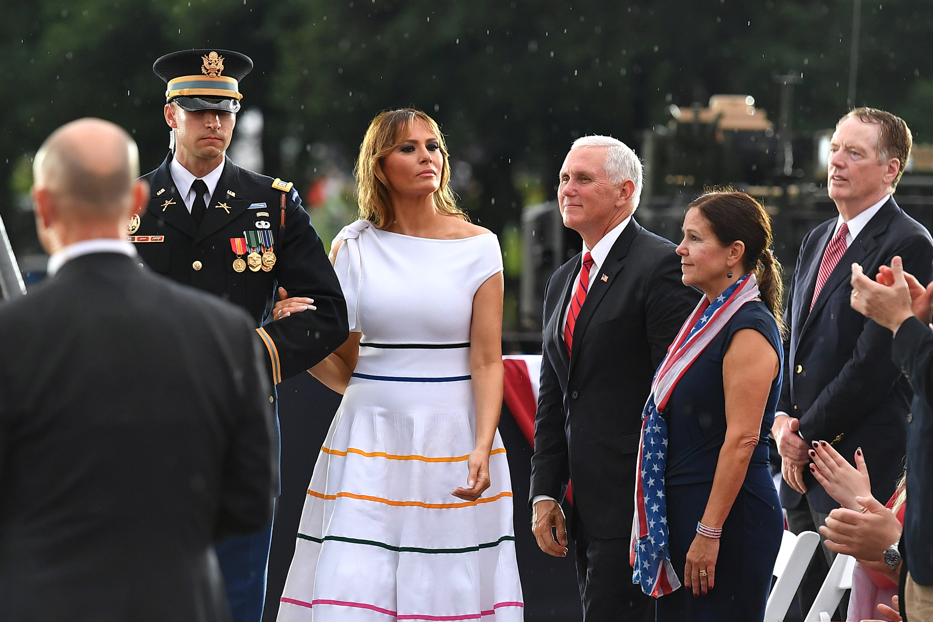 """US First Lady Melania Trump (C) is escorted to the stage during the """"Salute to America"""" Fourth of July event at the Lincoln Memorial in Washington, DC, July 4, 2019. (Photo by MANDEL NGAN / AFP)        (Photo credit should read MANDEL NGAN/AFP/Getty Images)"""