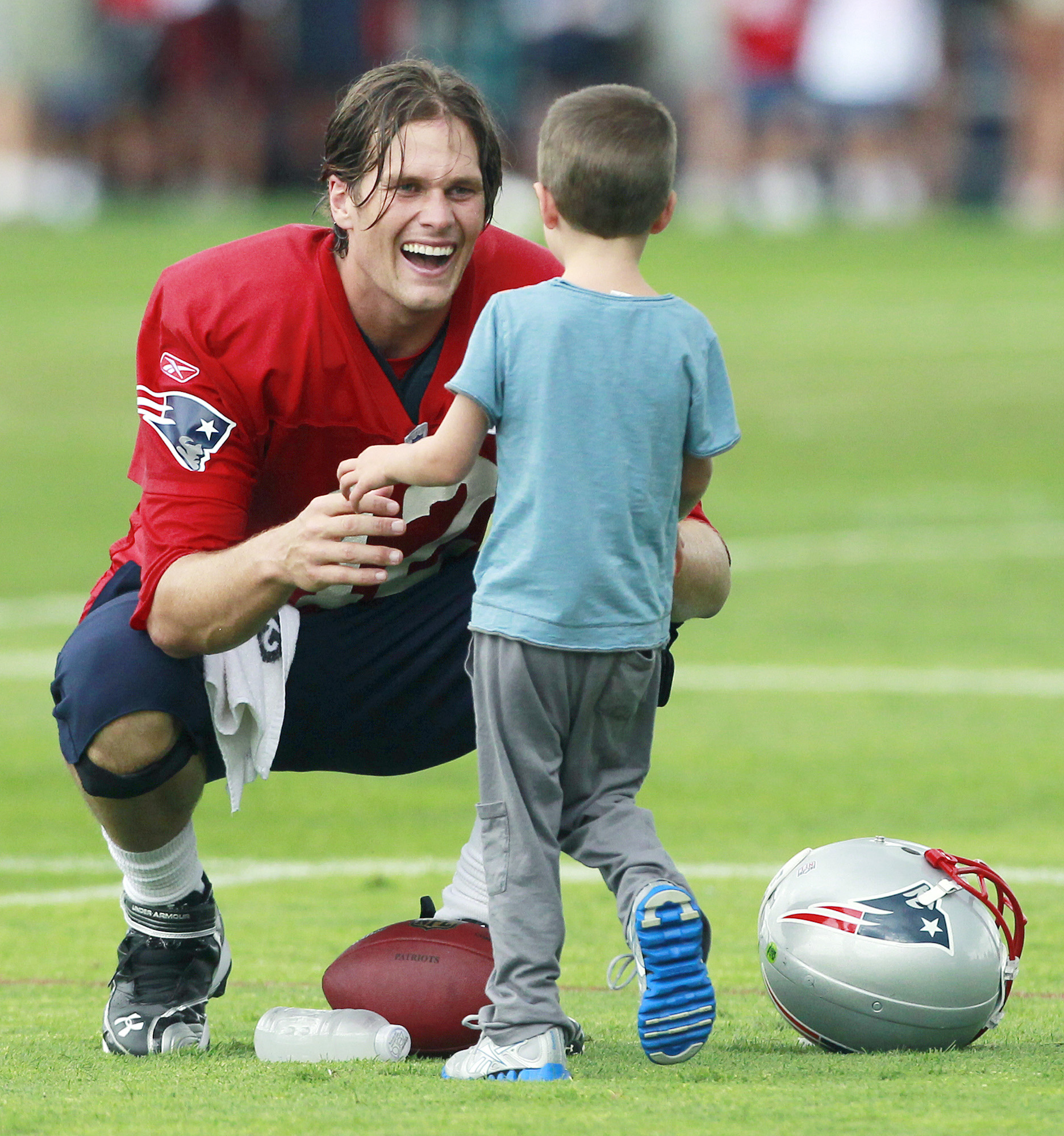 New England Patriots' Tom Brady greets his son Jack on the field after NFL football training camp Tuesday, Aug. 9, 2011, in Foxborough, Mass. (AP Photo/Michael Dwyer)