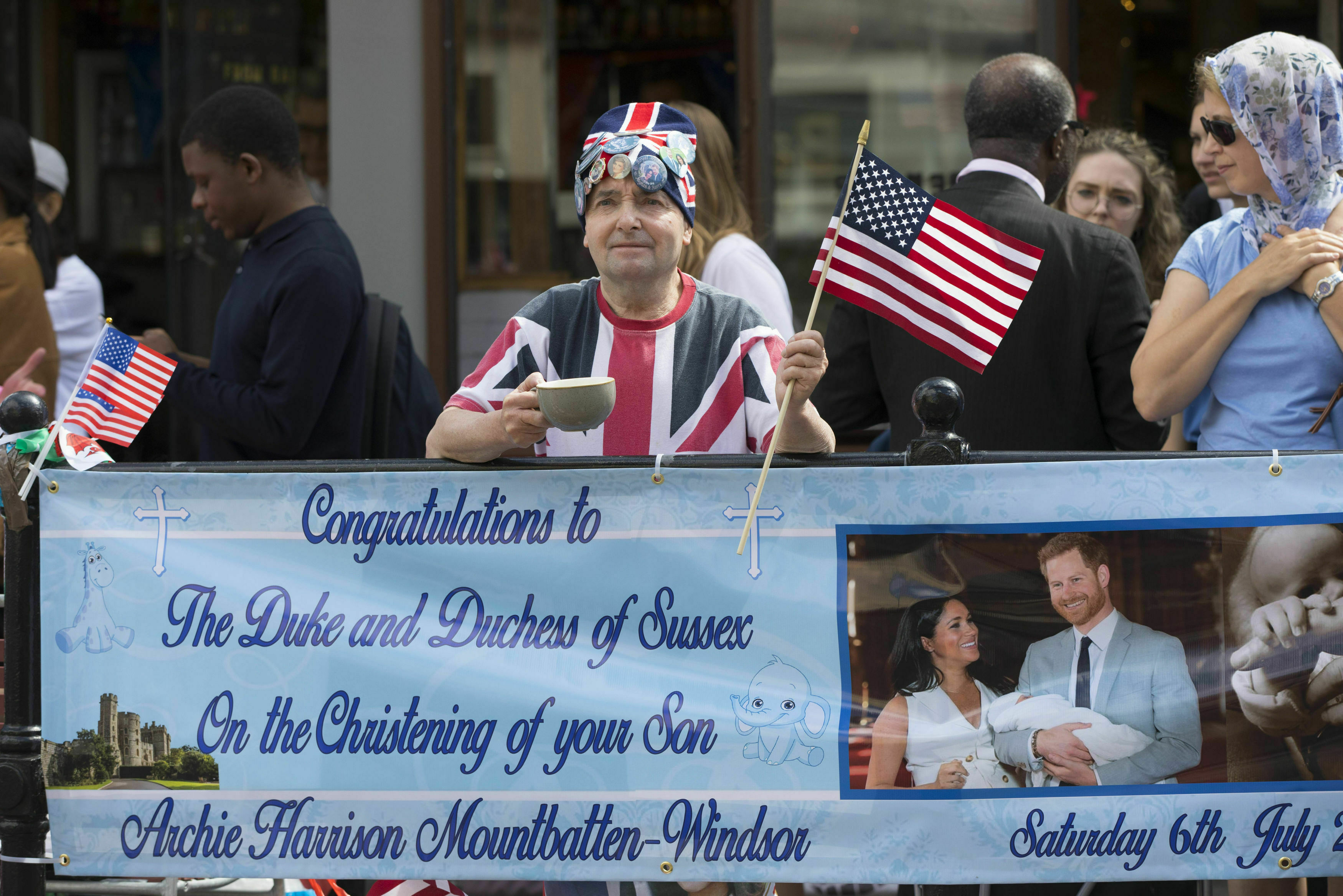 Royal superfan John Loughrey holds a sign in celebration of the royal christening of Archie, the son of Britain's Prince Harry and Meghan, Duchess of Sussex, outside Windsor Castle in England, Saturday, July 6, 2019. The 2-month-old son of the Duke and Duchess of Sussex will be baptized Saturday in a private chapel at the castle by Archbishop of Canterbury Justin Welby, head of the Church of England. (Rick Findler/PA via AP)