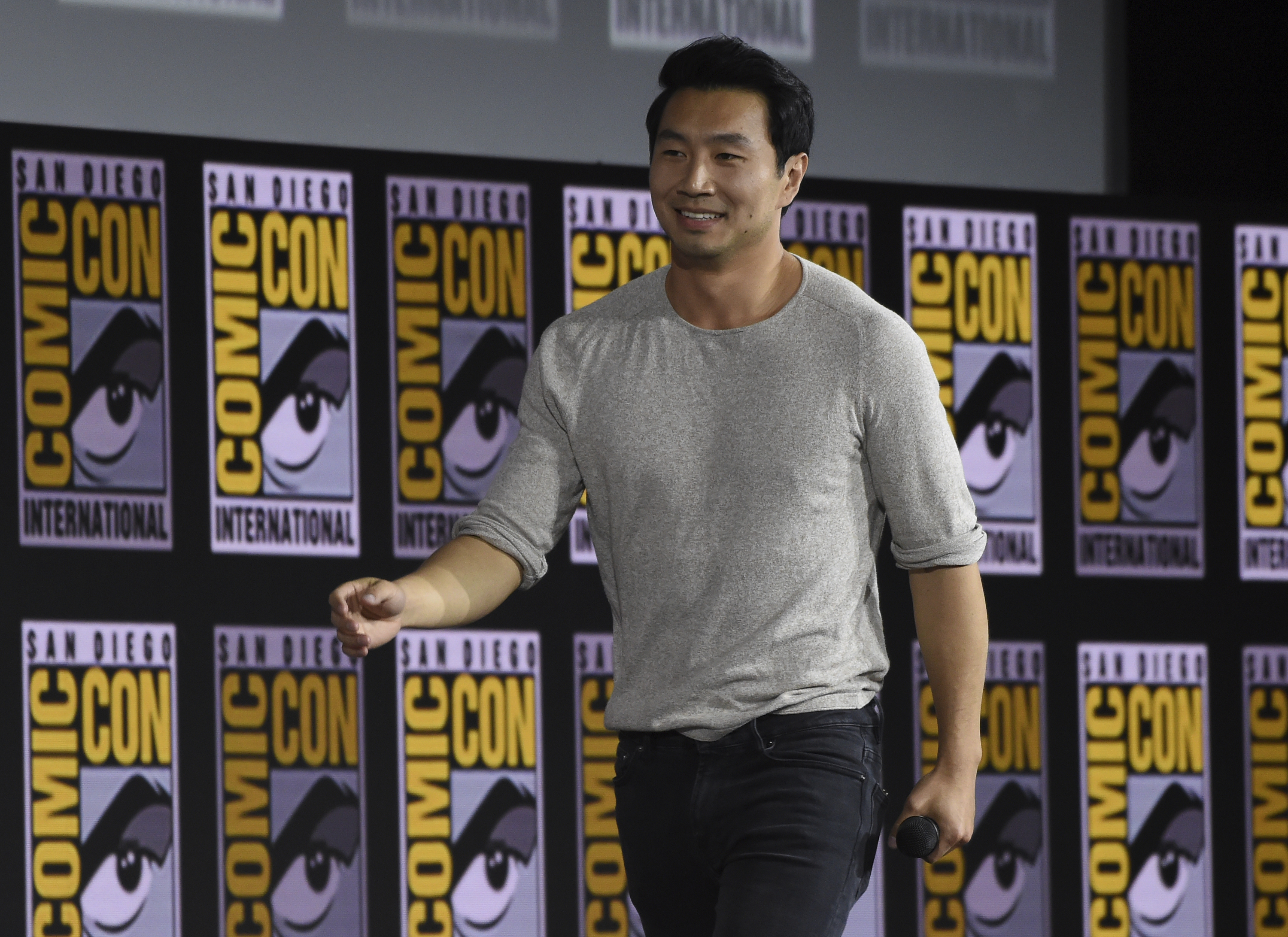 """Simu Liu walks on stage during the """"Shang-Chi and The Legend of the Ten Rings"""" portion of the Marvel Studios panel on day three of Comic-Con International on Saturday, July 20, 2019, in San Diego. (Photo by Chris Pizzello/Invision/AP)"""