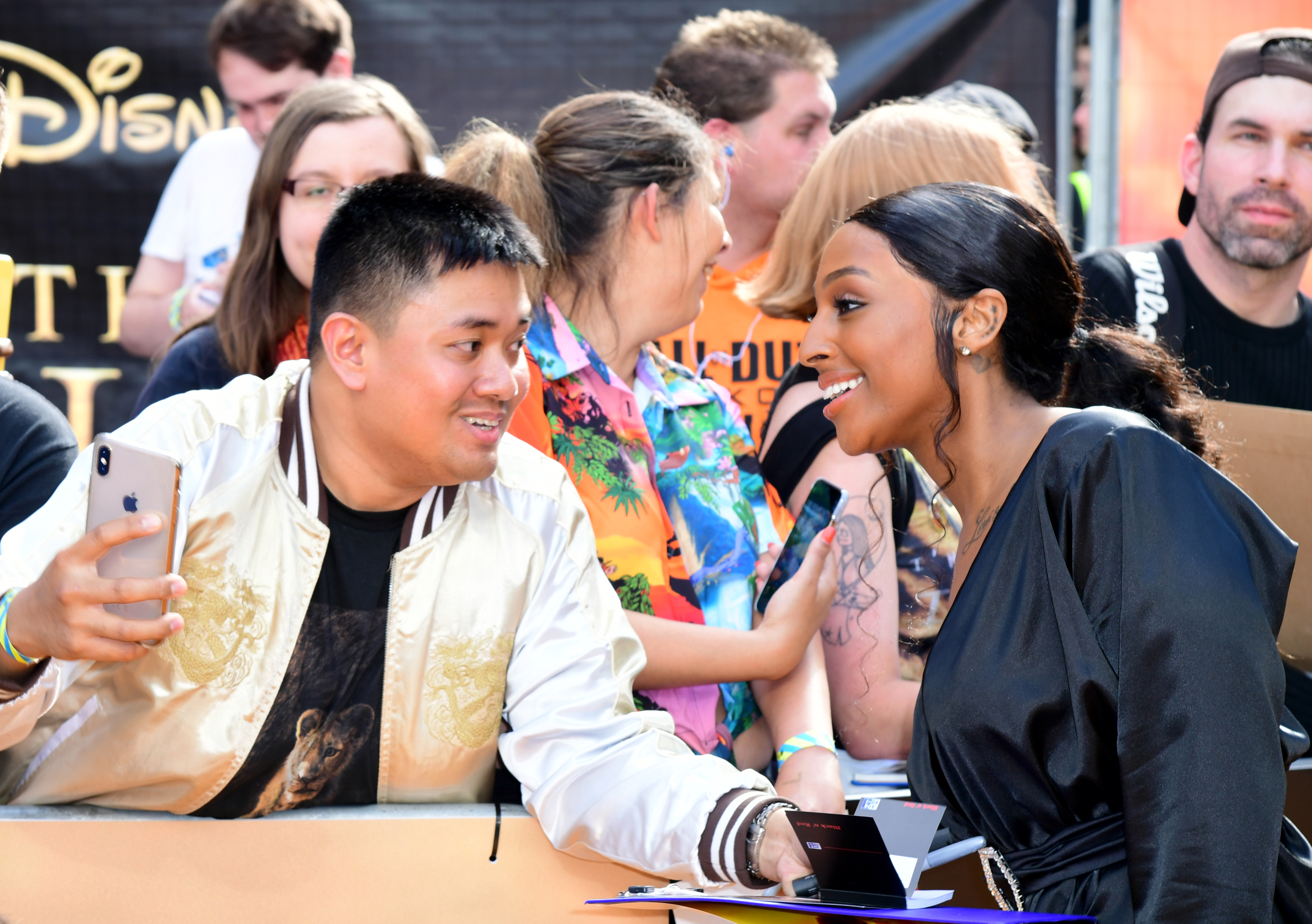 Alexandra Burke poses for a photograph with a fan during Disney's The Lion King European Premiere held in Leicester Square, London.