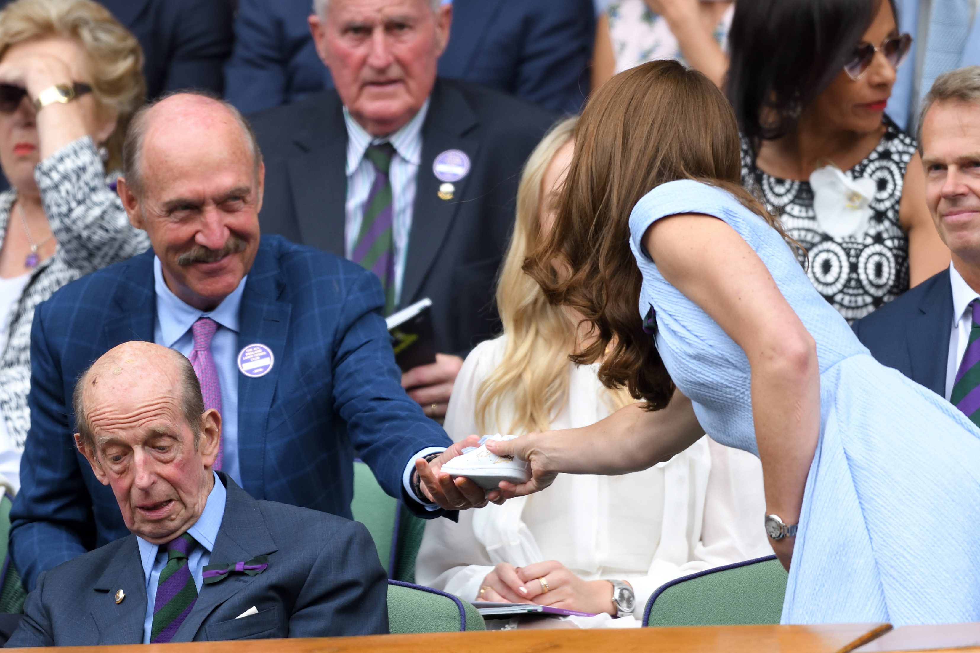 LONDON, ENGLAND - JULY 14: Stan Smith gives Catherine, Duchess of Cambridge a signed baby 'Stan Smith' trainer in the Royal Box during Men's Finals Day of the Wimbledon Tennis Championships at All England Lawn Tennis and Croquet Club on July 14, 2019 in London, England. (Photo by Karwai Tang/Getty Images)