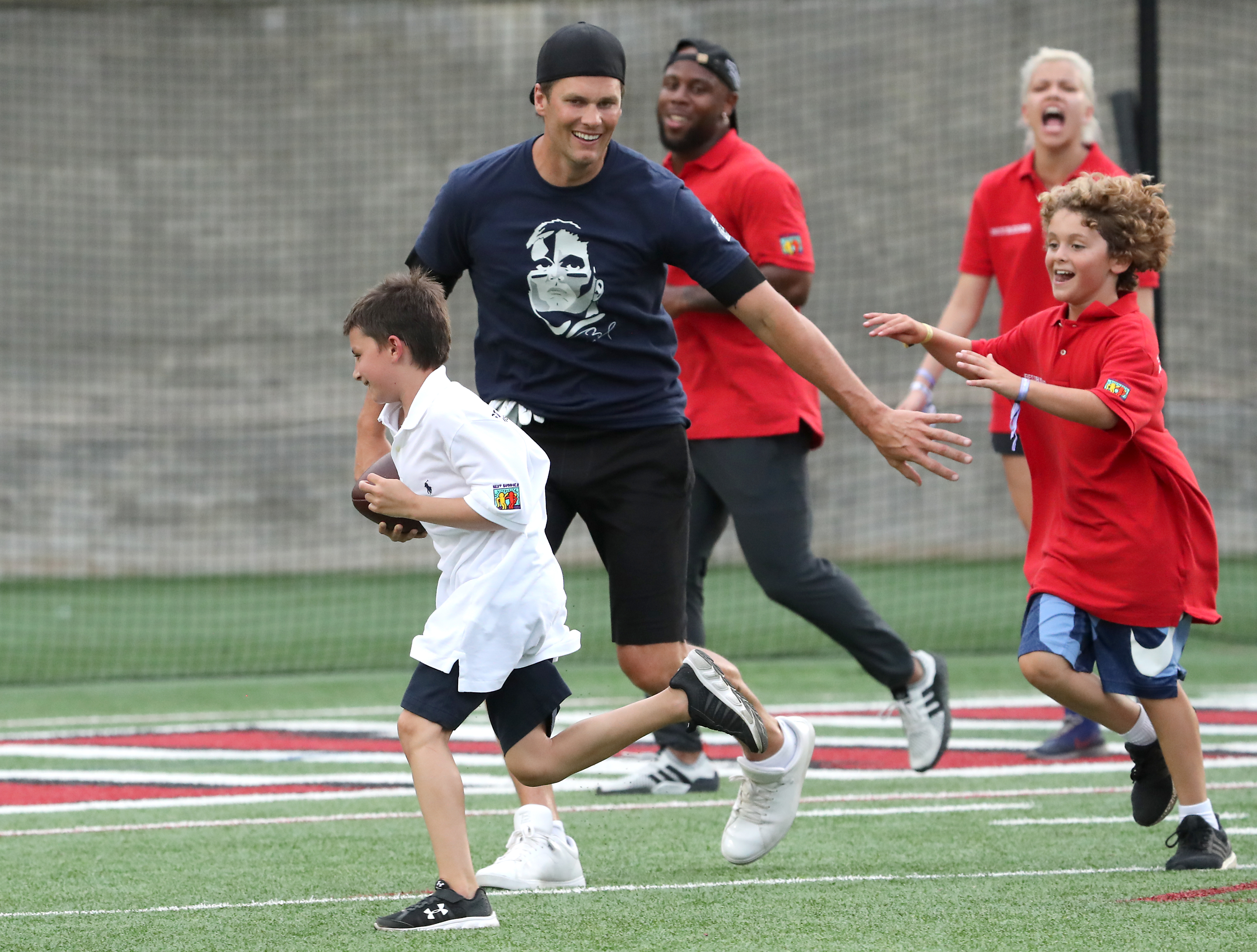 """BOSTON, MA - JUNE 1: New England Patriots quarterback Tom Brady blocks for his son, Benjamin as he scores a touchdown with pressure from John """"Joseph"""" Sargent Shriver during the Best Buddies Football Challenge with at Harvard Stadium in Boston on June 1, 2018. (Photo by Matthew J. Lee/The Boston Globe via Getty Images)"""