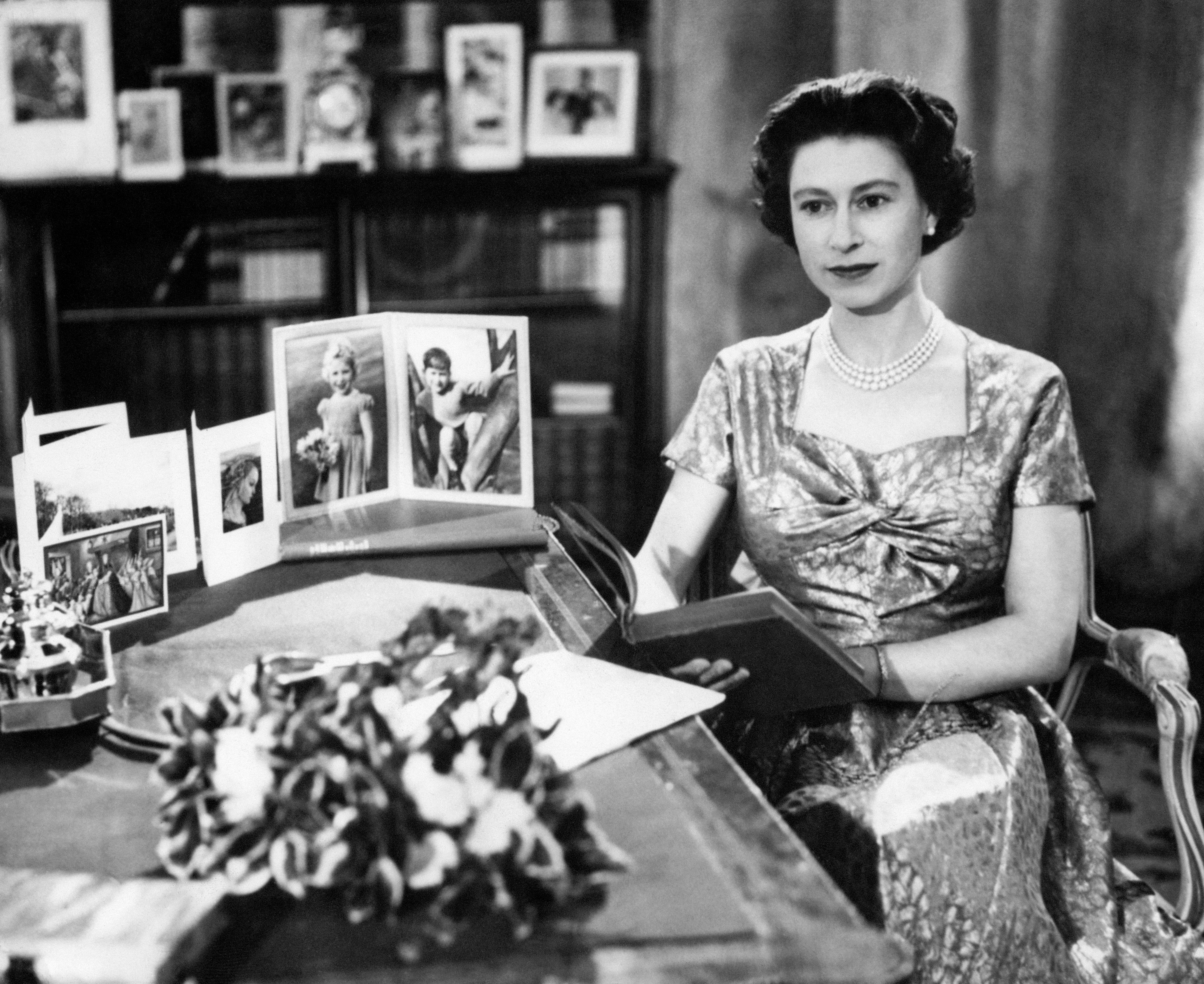 The Queen, in a gold lame dress, is seen in the Long Library at Sandringham shortly after making the traditional Christmas Day broadcast to the nation. On the desk are portraits of Prince Charles and Princess Anne. The Queen is holding the copy of 'Pilgrim's Progress', from which she read a few lines during her message. The broadcast was televised this year for the first time and was carried by both the BBC and ITV. It was the 25th anniversary of the first radio message to the Commonwealth by her grandfather, King George V.
