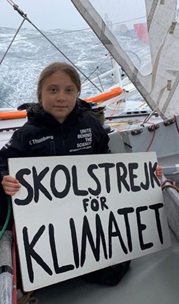 """Swedish climate activist Greta Thunberg holding signage reading """"School strike for climate"""" sits aboard Team Malizia yacht that will transport Thunberg across the Atlantic for the UN Climate Action Conference in this recent undated photo released August 16, 2019. Team Malizia/Handout via REUTERS  THIS IMAGE HAS BEEN SUPPLIED BY A THIRD PARTY. MANDATORY CREDIT."""