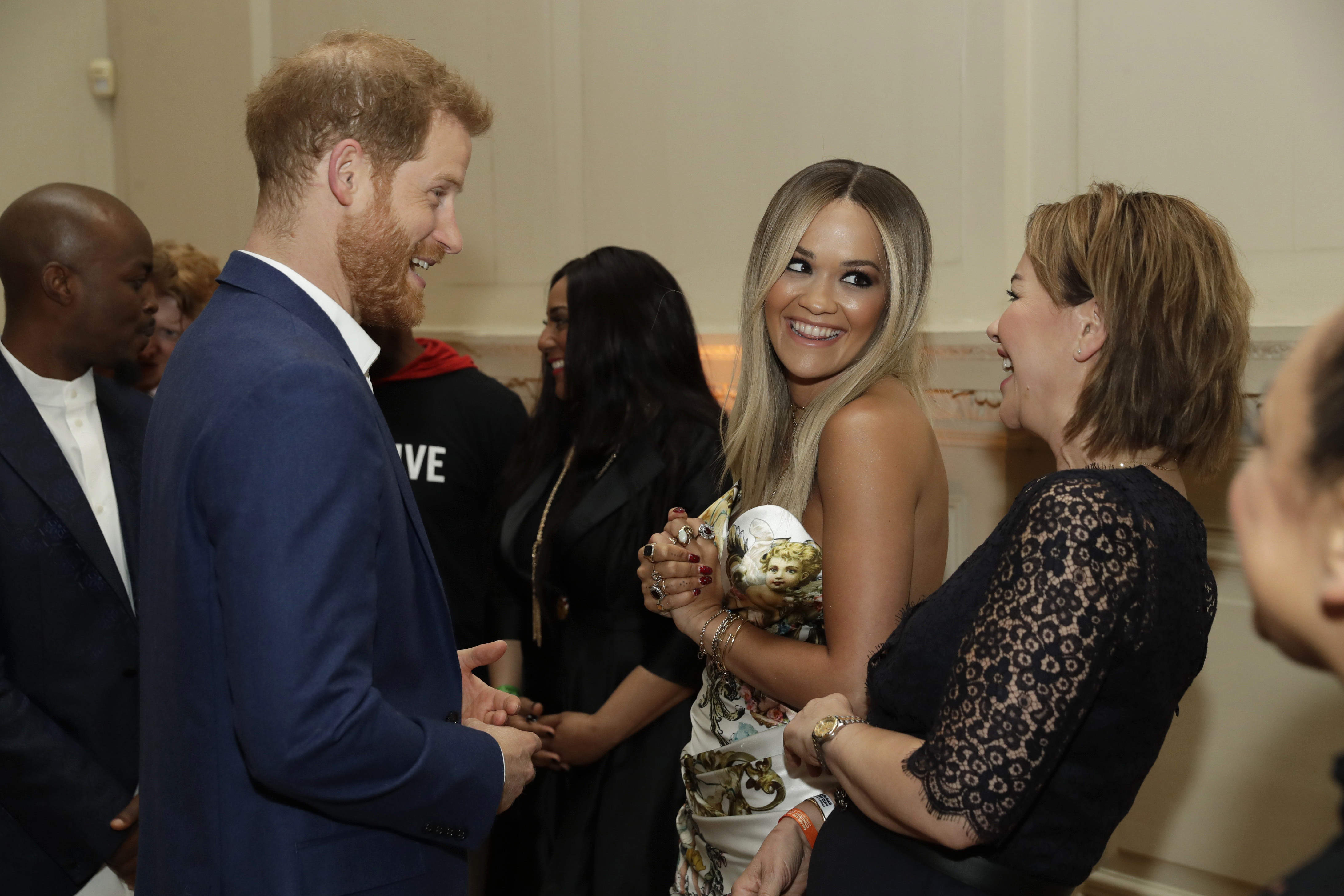The Duke of Sussex speaks to singer Rita Ora and her mum Vera Sahatciu during a reception before a concert hosted by Sentebale in Hampton Court Palace in East Molesey, to raise awareness and vital funds for the Duke's charity, Sentebale, which helps young people in southern Africa affected by HIV.