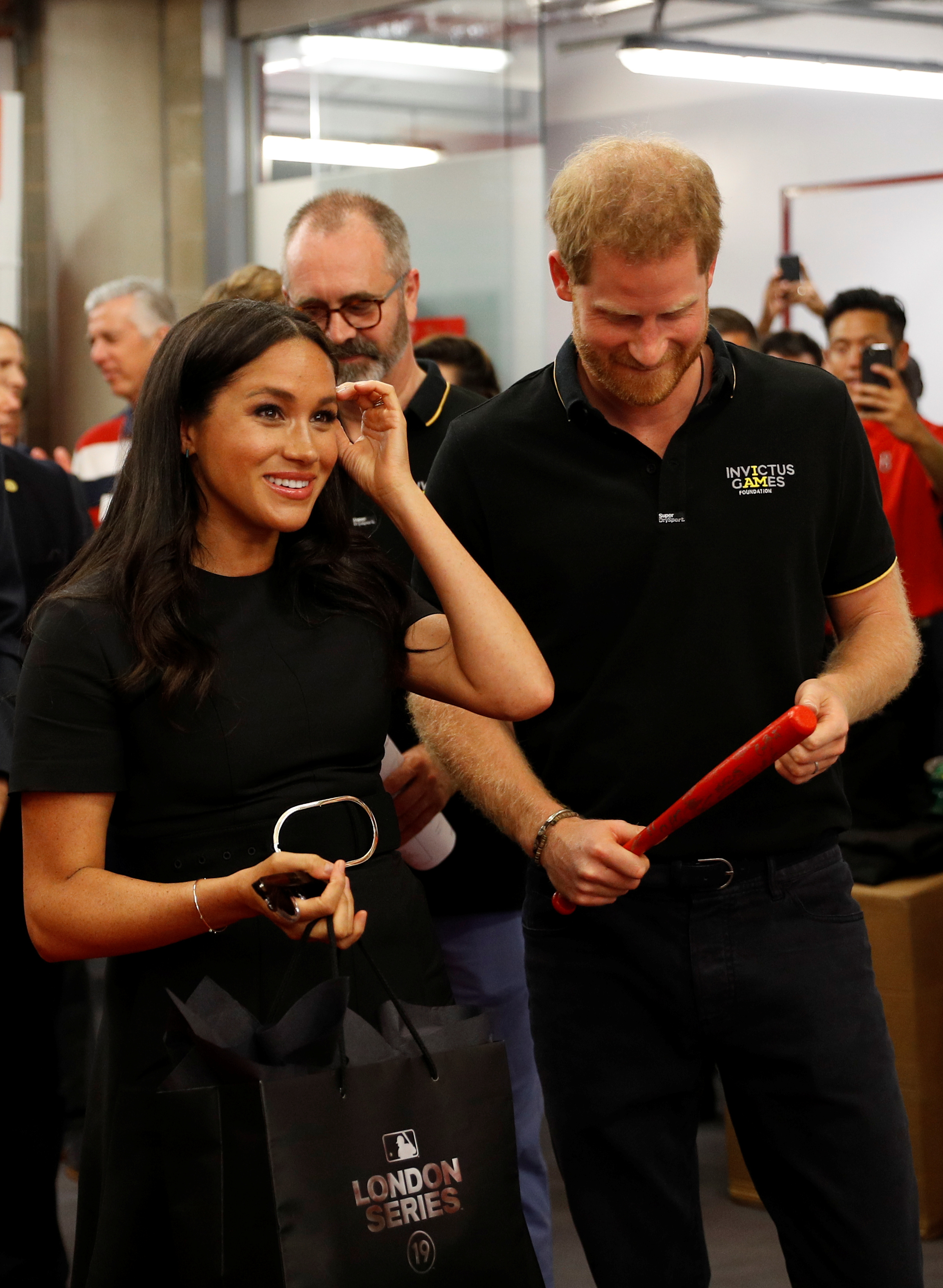 The Duke and Duchess of Sussex receive presents for their son Archie as they meet players of the Boston Red Sox as they attend the Boston Red Sox vs New York Yankees baseball game at the London Stadium in support of the Invictus Games Foundation.