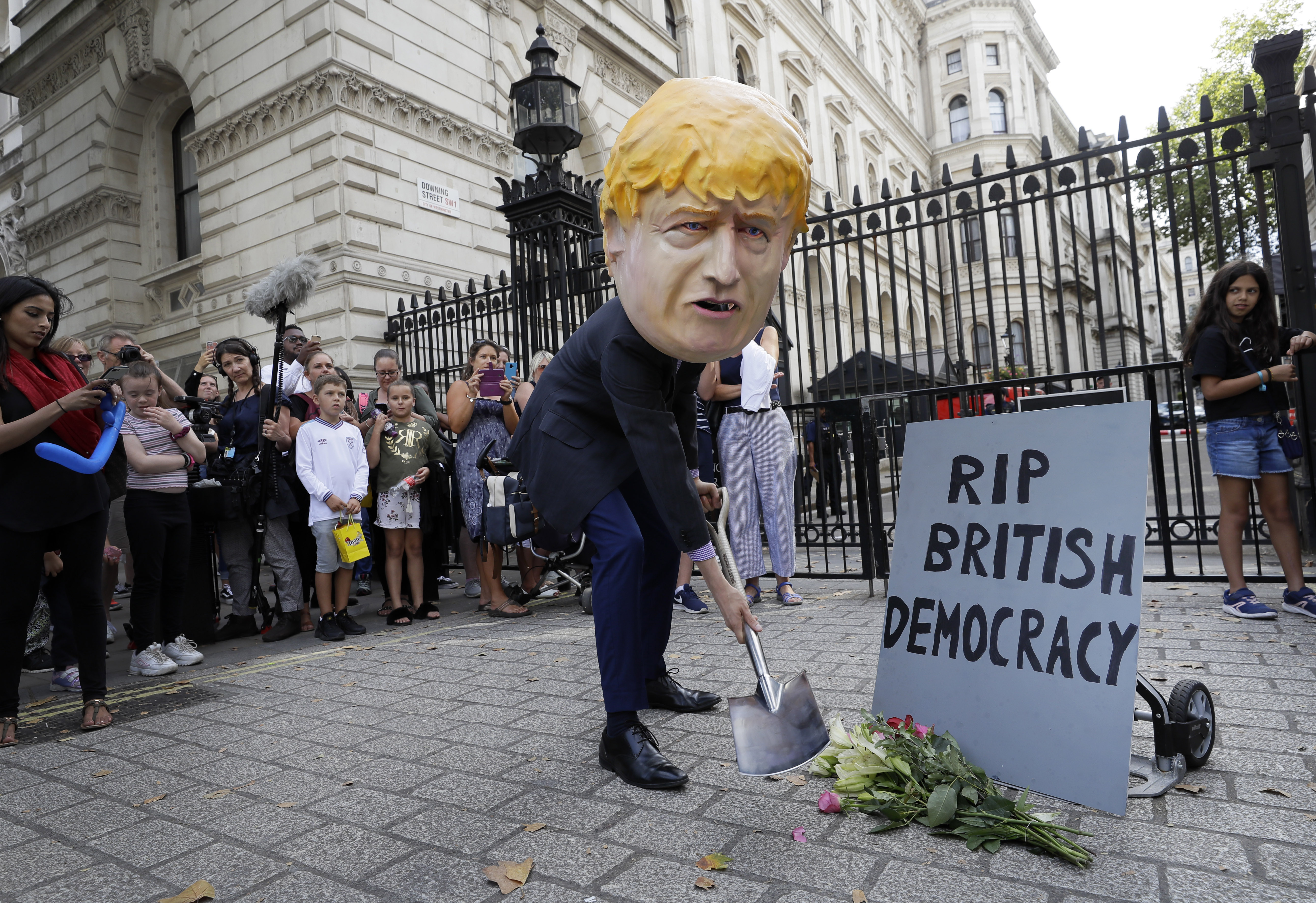 A man in a giant Boris Johnson 'head' digs a grave at the foot of a pretend tombstone outside Downing Street in London, Wednesday, Aug. 28, 2019. Britain's Queen Elizabeth II has approved the U.K. government's request to suspend Parliament amid a growing crisis over Brexit. Prime Minister Boris Johnson spoke to the queen on Wednesday to request an end to the current Parliament session in September.(AP Photo/Kirsty Wigglesworth)