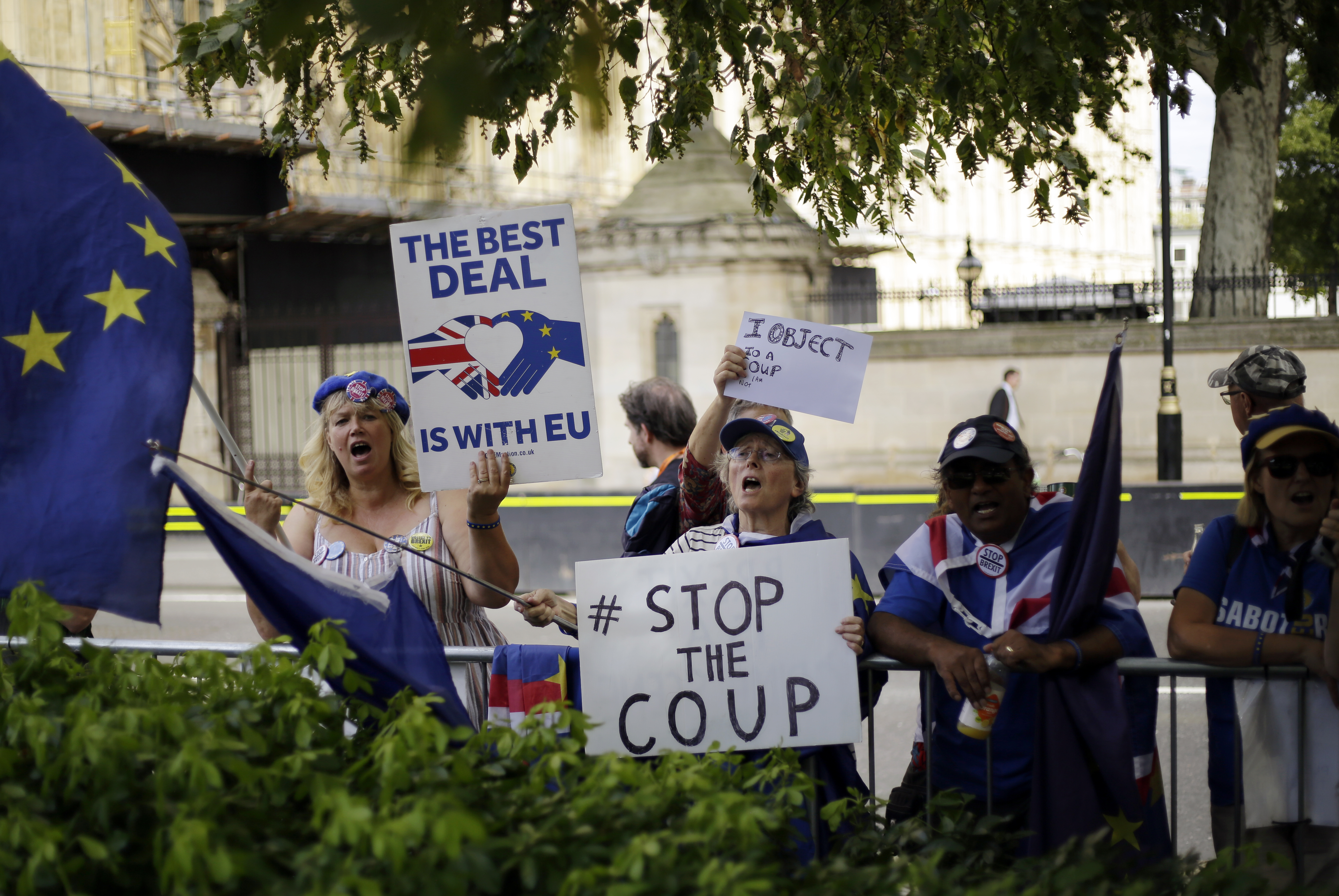 Anti-Brexit supporters wave flags and hold signs near the Houses of Parliament in central London, Wednesday, Aug. 28, 2019. British Prime Minister Boris Johnson asked Queen Elizabeth II on Wednesday to suspend Parliament, throwing down the gauntlet to his critics and causing outrage among opposition leaders who will have even less time to thwart a no-deal Brexit. (AP Photo/Matt Dunham)