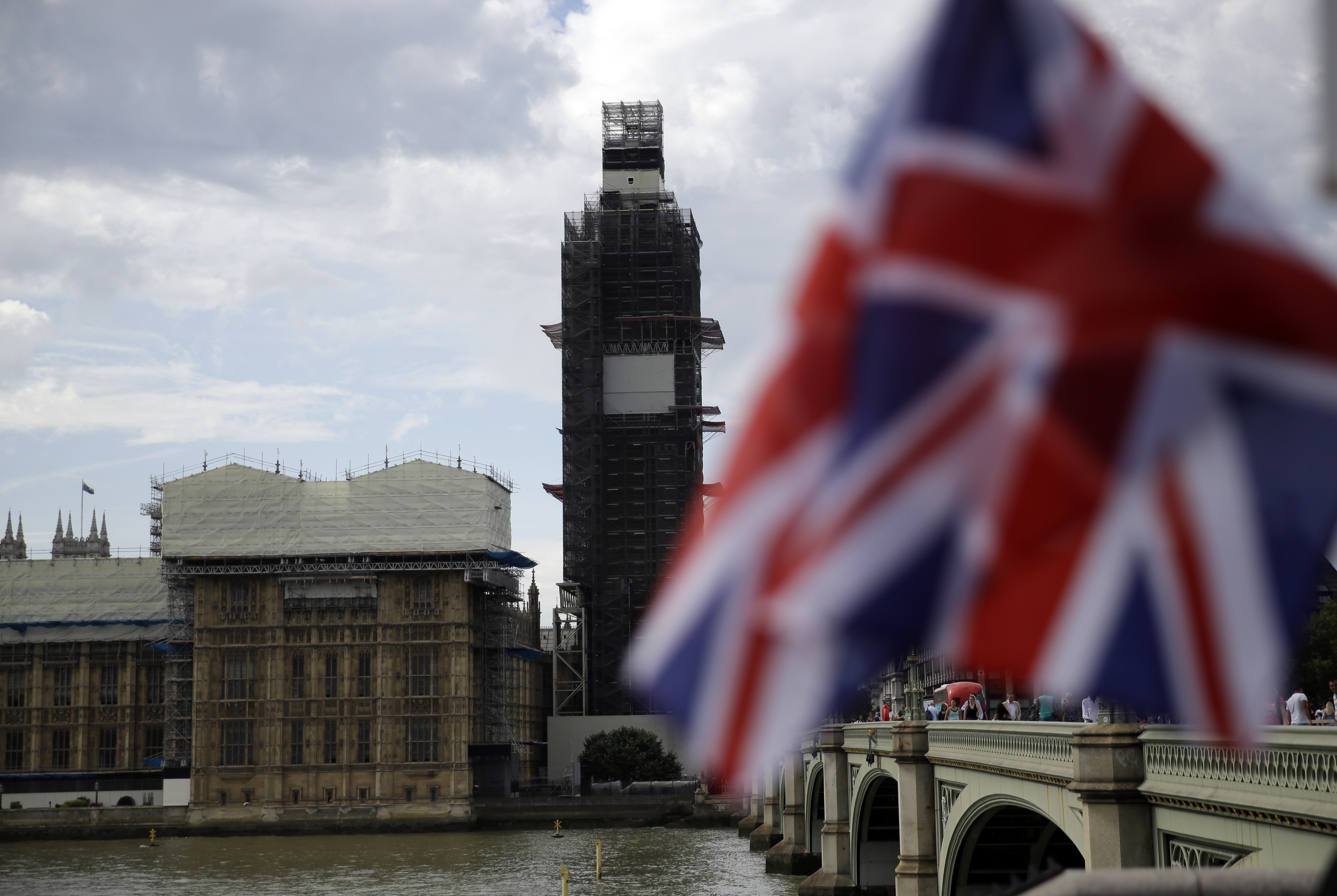 The Houses of Parliament are seem, with a Union Jack flag in the foreground, in central London, Wednesday, Aug. 28, 2019. British Prime Minister Boris Johnson asked Queen Elizabeth II on Wednesday to suspend Parliament, throwing down the gauntlet to his critics and causing outrage among opposition leaders who will have even less time to thwart a no-deal Brexit. (AP Photo/Matt Dunham)