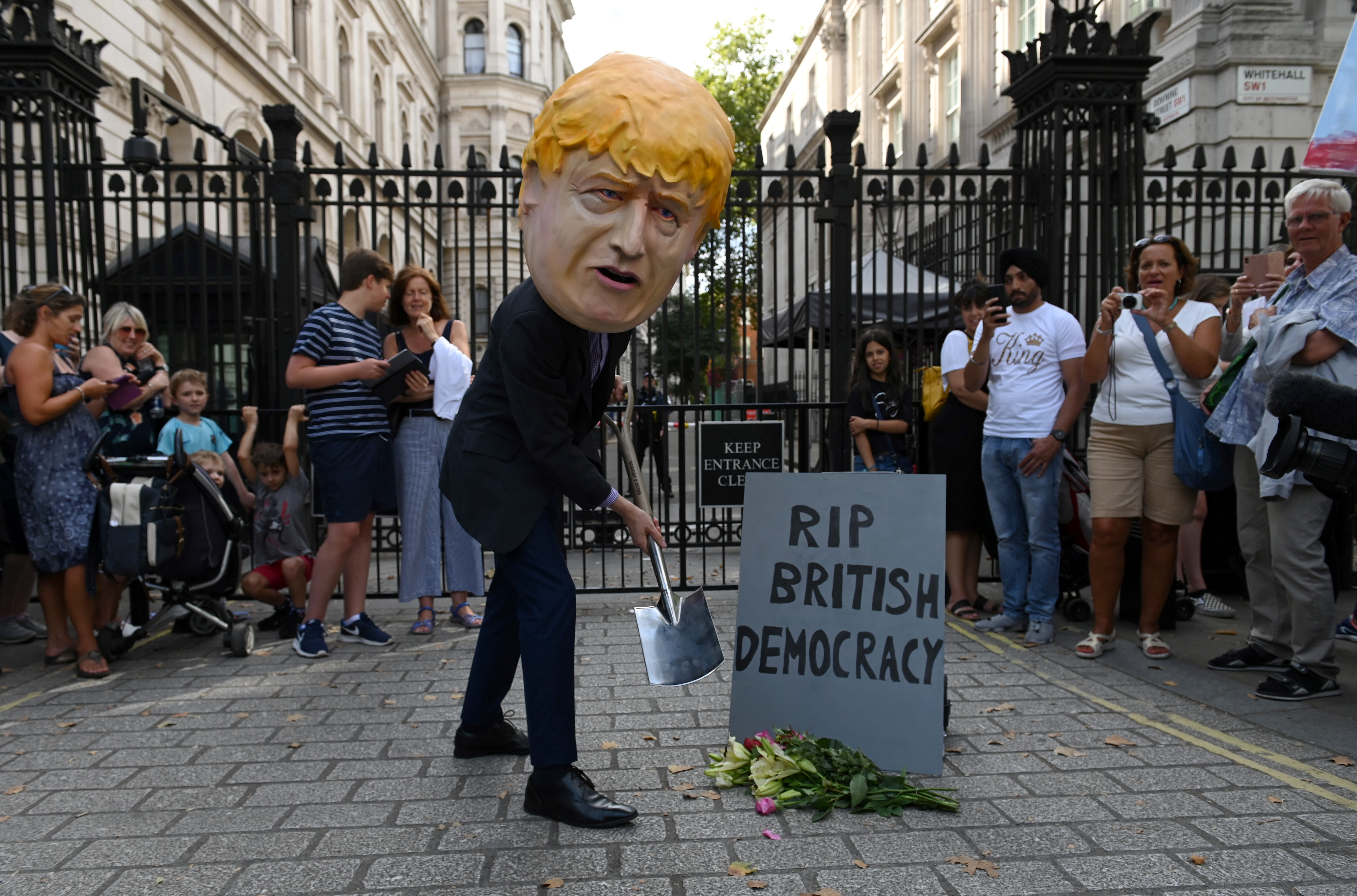 """An demonstrator, wearing a mask depicting Britain's Prime Minister Boris Johnson, and a mock gravestone inscribed with the words """"RIP British Democracy"""" protests outside the gates to Downing Street in central London on August 28, 2019. - British Prime Minister Boris Johnson announced Wednesday that the suspension of parliament would be extended until October 14 -- just two weeks before the UK is set to leave the EU -- enraging anti-Brexit MPs. MPs will return to London later than in recent years, giving pro-EU lawmakers less time than expected to thwart Johnson's Brexit plans before Britain is due to leave the European Union on October 31. (Photo by DANIEL LEAL-OLIVAS / AFP)        (Photo credit should read DANIEL LEAL-OLIVAS/AFP/Getty Images)"""