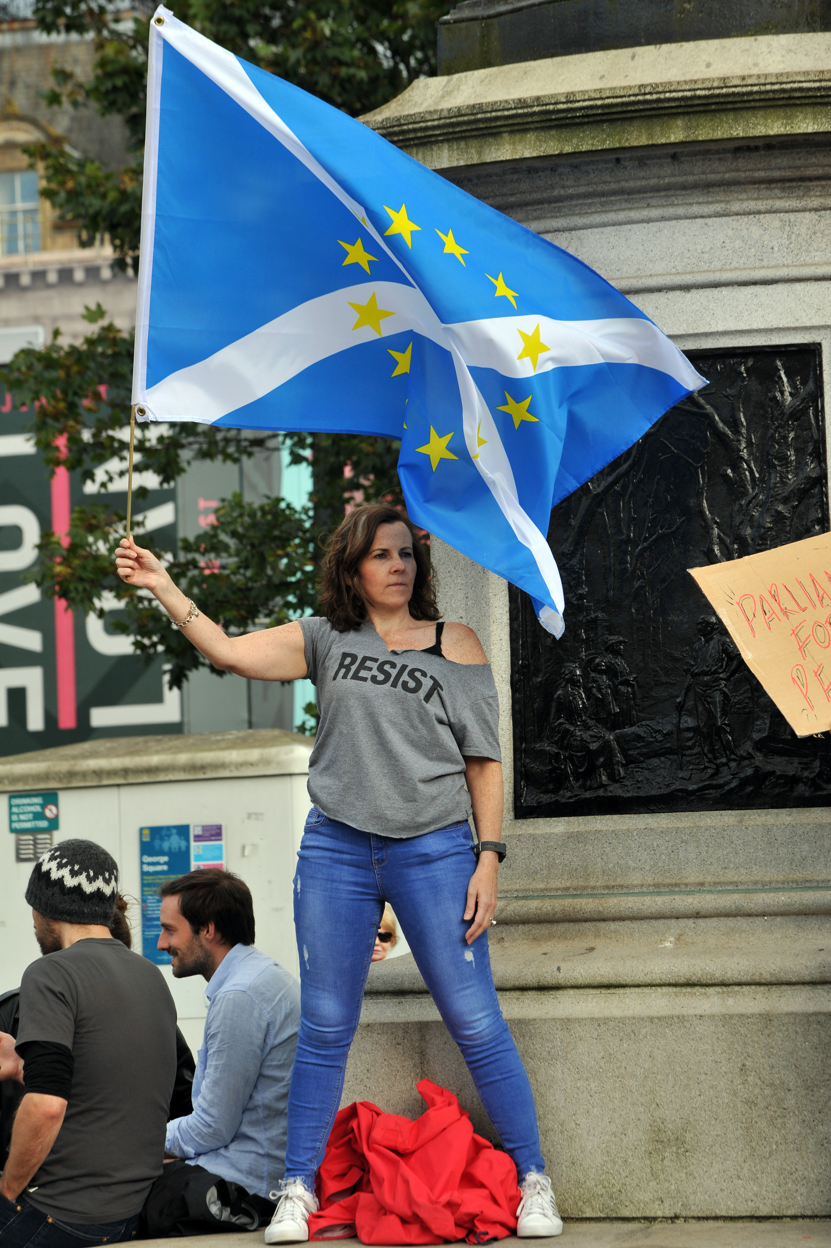 """A demonstrator flies a Scottish Saltire EU composite flag during a protest against the British government's move to suspend parliament in the final weeks before Brexit in Glasgow on August 31, 2019. - Demonstrations, being dubbed """"Stop The Coup"""" by organisers, were to be held across Britain on August 31 against Prime Minister Boris Johnson's move to suspend parliament in the final weeks before Brexit. The protests come ahead of an intense political week in which Johnson's opponents will seek to block the move in court and legislate against a no-deal departure from the European Union. (Photo by Andy Buchanan / AFP)        (Photo credit should read ANDY BUCHANAN/AFP/Getty Images)"""