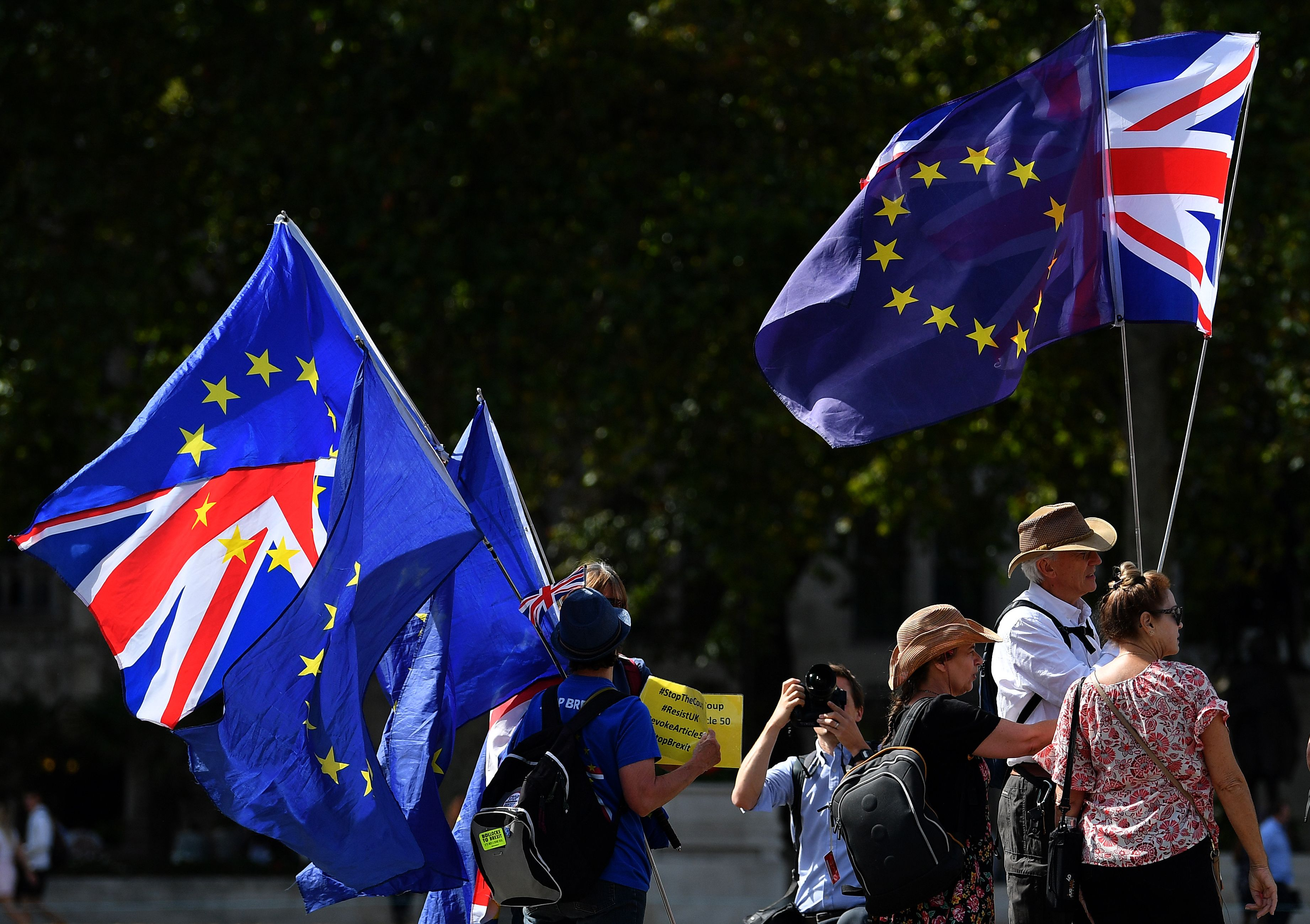 Anti-Brexit activists hold Union and EU flags as they demonstrate opposite the Houses of Parliament in Westminster, London on August 29, 2019. - Prime Minister Boris Johnson's suspension of parliament weeks before Britain's EU departure date faced legal challenges on Thursday following a furious outcry from pro-Europeans and MPs opposed to a no-deal Brexit. (Photo by DANIEL LEAL-OLIVAS / AFP)        (Photo credit should read DANIEL LEAL-OLIVAS/AFP/Getty Images)