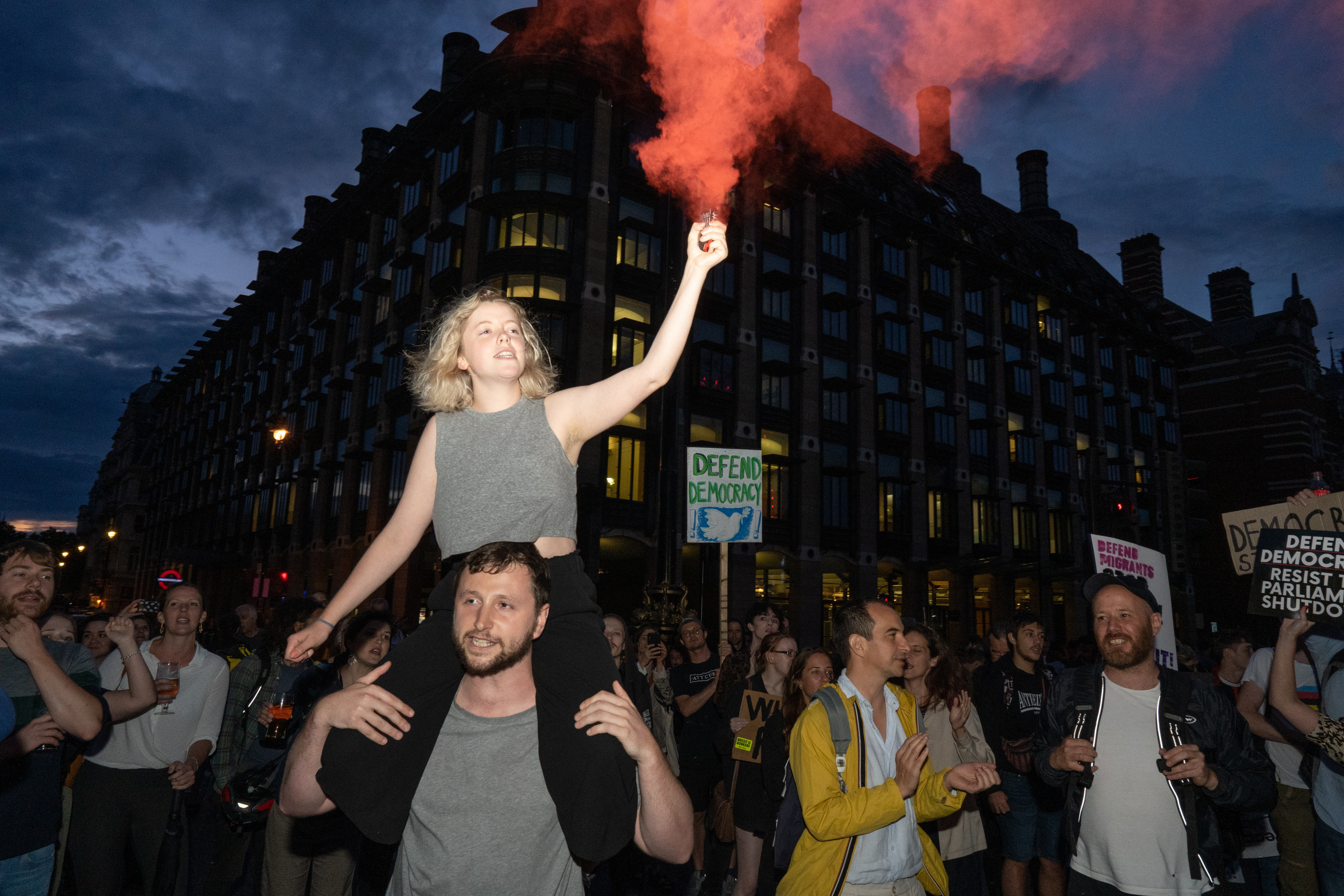 A woman is seen with a flare on westminster bridge outside the houses of parliament where hundreds of people are seen protesting against Boris Johnson