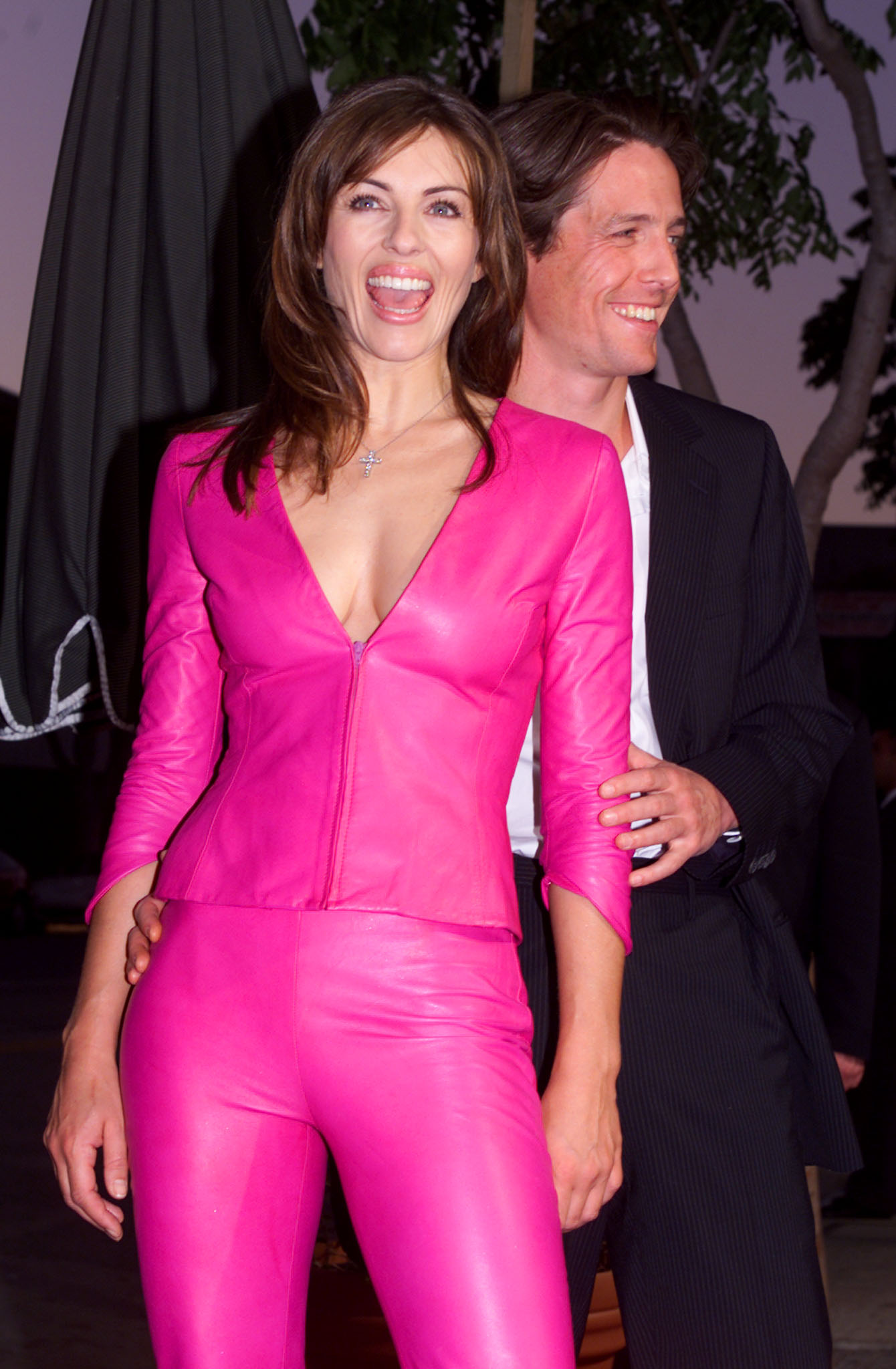 """Hugh Grant, star of the new romantic comedy film """" Mickey Blue Eyes"""" poses with girlfriend Elizabeth Hurley as they arrive for the film's Los Angeles premiere August 17. Hurley, wearing a shocking pink Versace pantsuit, produced the film, which features Grant as an English art dealer who becomes involved in outrageous criminal activity with his girlfriend's Mob-connected father.  FSP/AA"""
