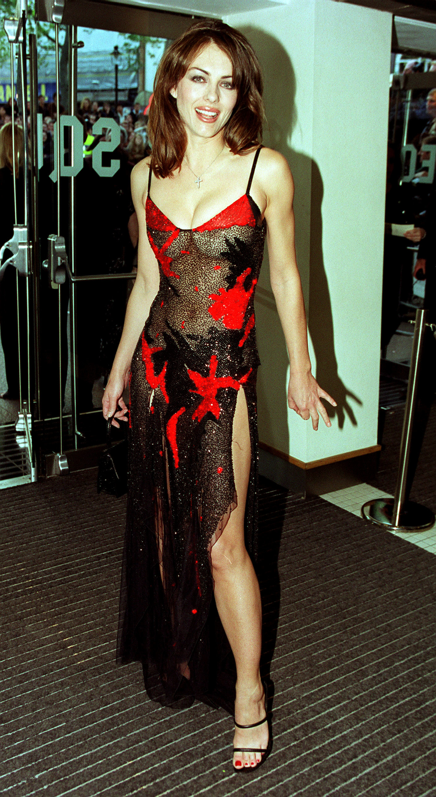 """Model and film star, Elizabeth Hurley, arriving for the World Premiere of """"Notting Hill"""" wearing a Versace dress, at the Odeon Leicester Square."""