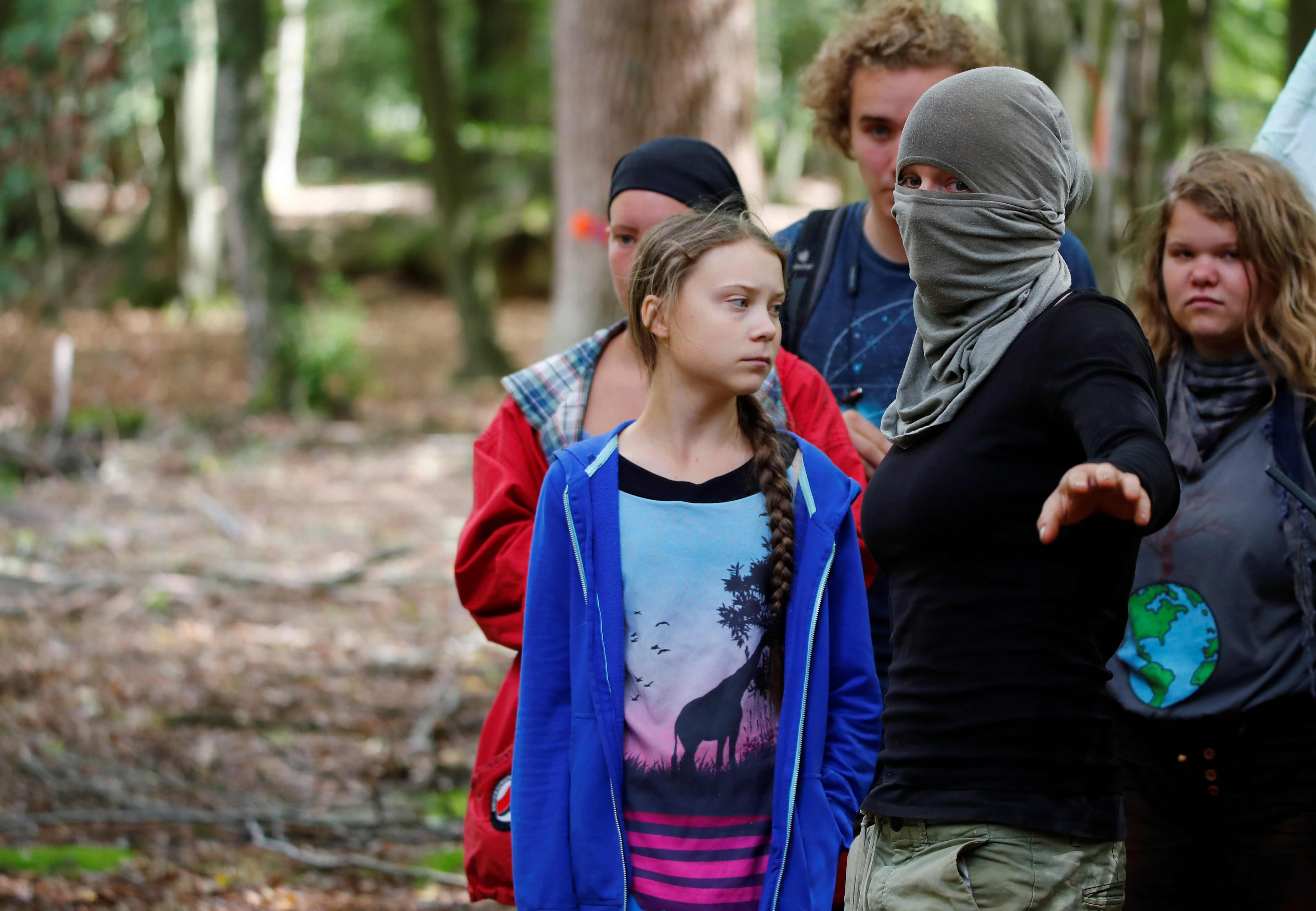 """Greta Thunberg, Swedish """"Fridays for Future"""" climate activist, stands next to activists and a masked inhabitant of an illegal tree house in the Hambach Forest that is supposed to be chopped away for the nearby open-cast brown coal minr of German utility RWE, west of Cologne, Germany, August 10, 2019. REUTERS/Wolfgang Rattay"""