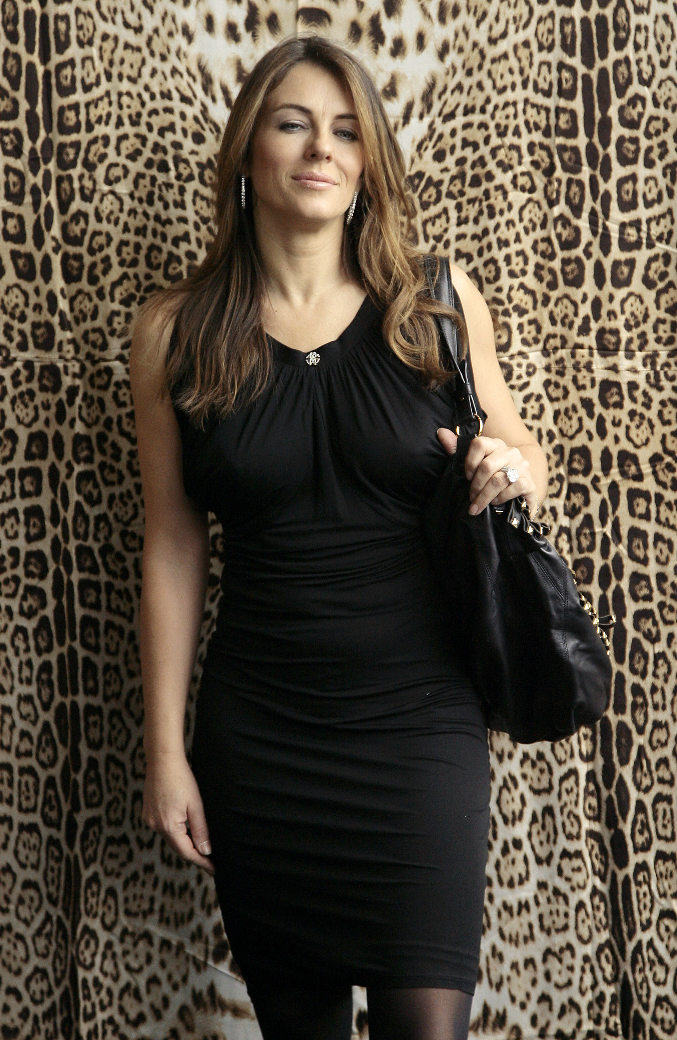 British model Elizabeth Hurley poses for photographers as she arrives to attend the Roberto Cavalli Fall/Winter 2009/10 women's collection during Milan Fashion Week March 1, 2009 REUTERS/Alessandro Garofalo  (ITALY)