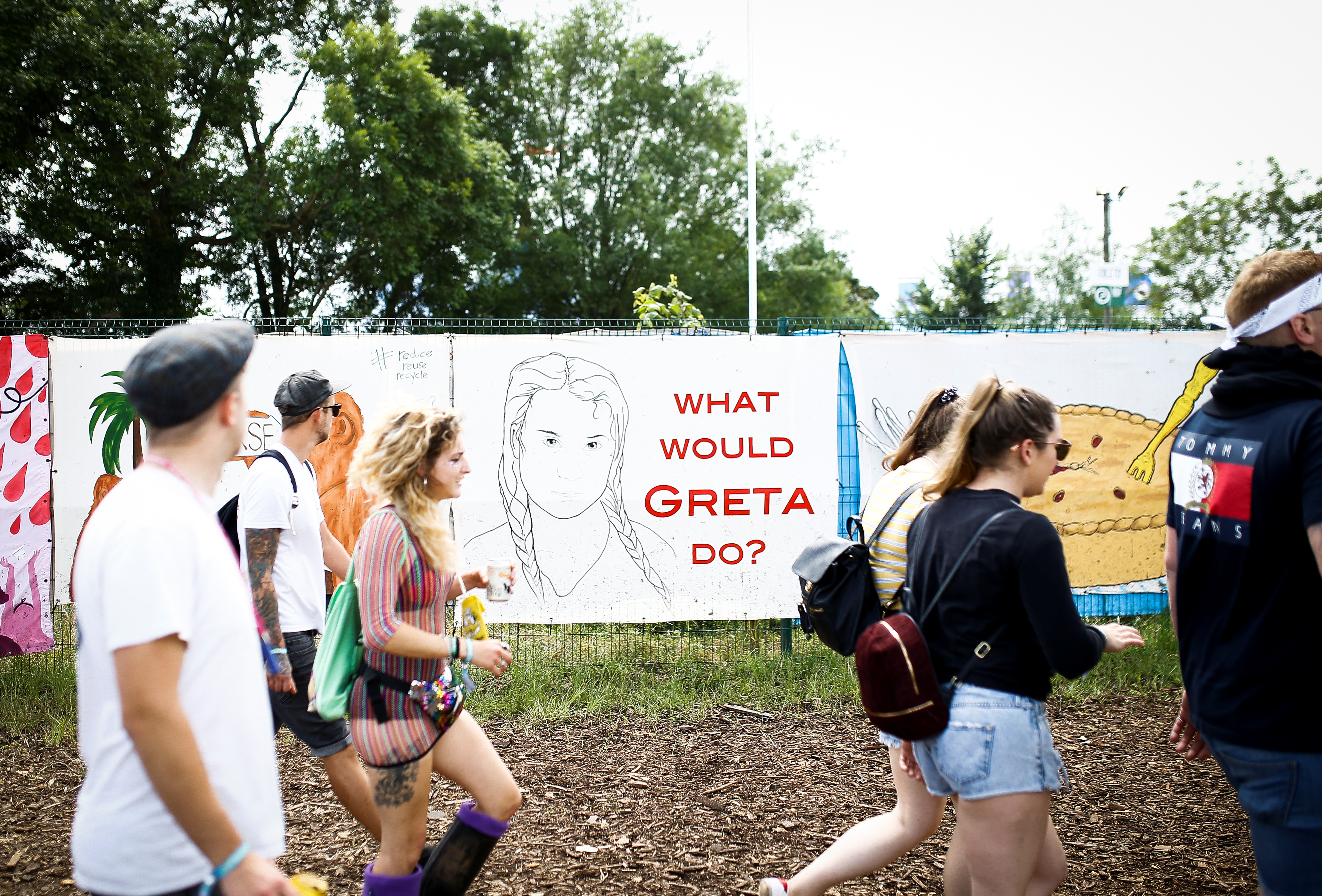 Revellers walk past a Greta Thunberg mural at Glastonbury Festival at Worthy farm in Somerset, Britain June 26, 2019. REUTERS/Henry Nicholls