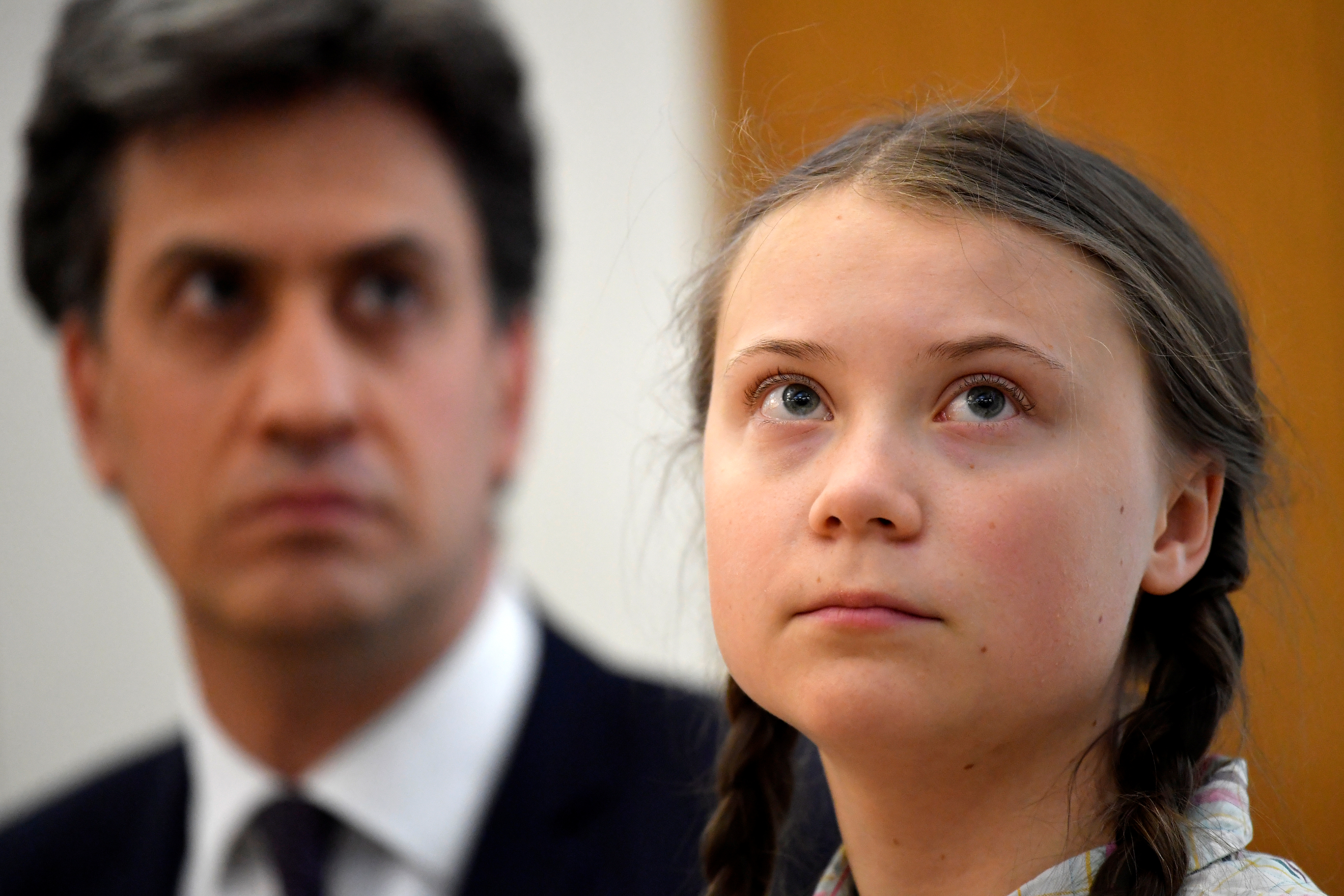 Swedish environmental activist Greta Thunberg looks on next to the former leader of Britain's opposition Labour Party Ed Miliband at the House of Commons as guest of Caroline Lucas, in London, Britain April 23, 2019. REUTERS/Toby Melville