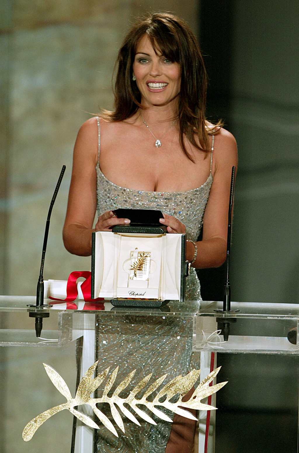 """British actress Elizabeth Hurley smiles during the presentation of the Best Actor award during the closing ceremony at the 56th International Film Festival in Cannes, May 25, 2003. [Turkish actors Muzaffer Ozdemir and Mehmet Emin Toprak, winners for their roles in Turkish director Nuri Bilge Ceylan's film entry """"Uzak"""", were not present at the ceremony.]"""