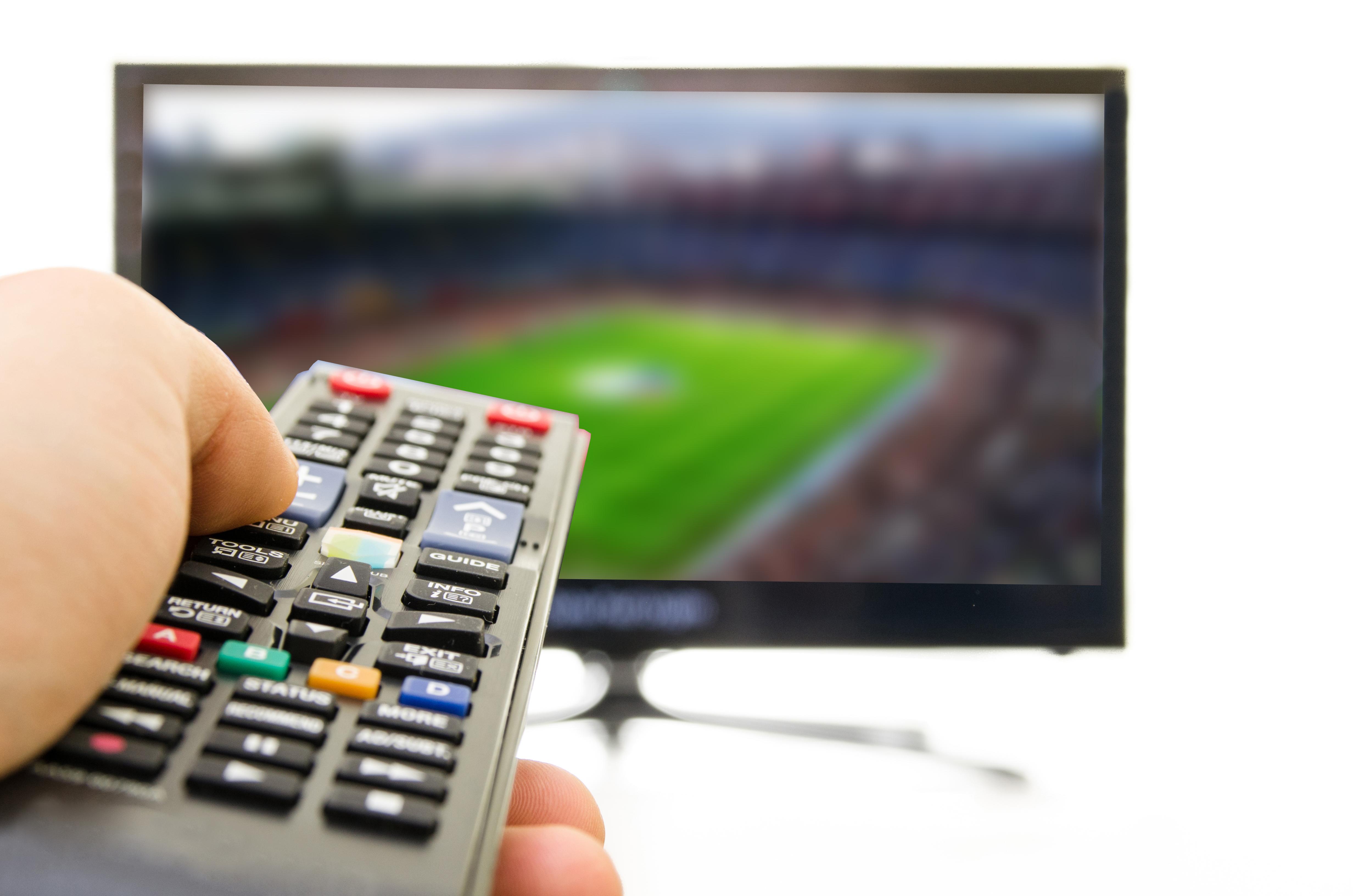 Controle remoto de televisão vendo futebol