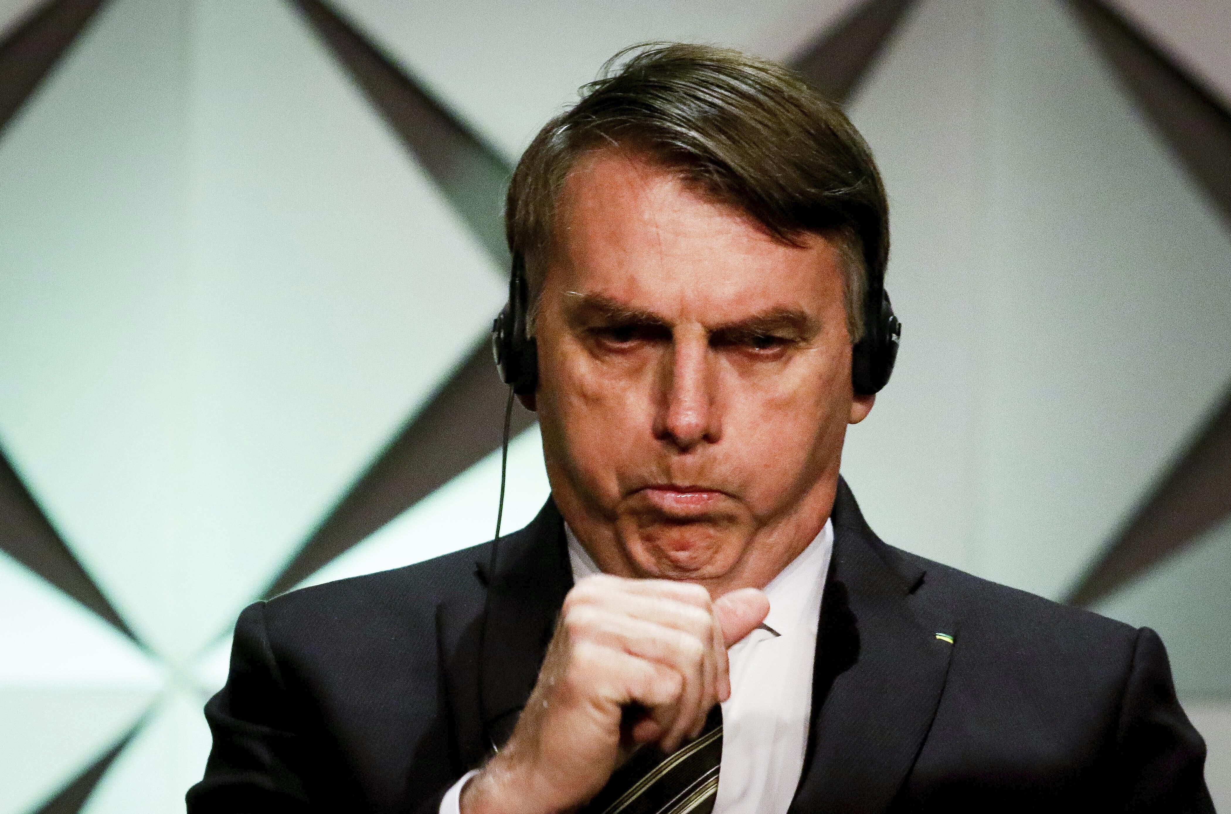 A imagem mostra o presidente Jair Messias Bolsonaro durante a Abertura Oficial do Fórum de Investimentos Brasil 2019, usando fones de ouvido de tradução simultânea enquanto cobre a boca para tossir.
