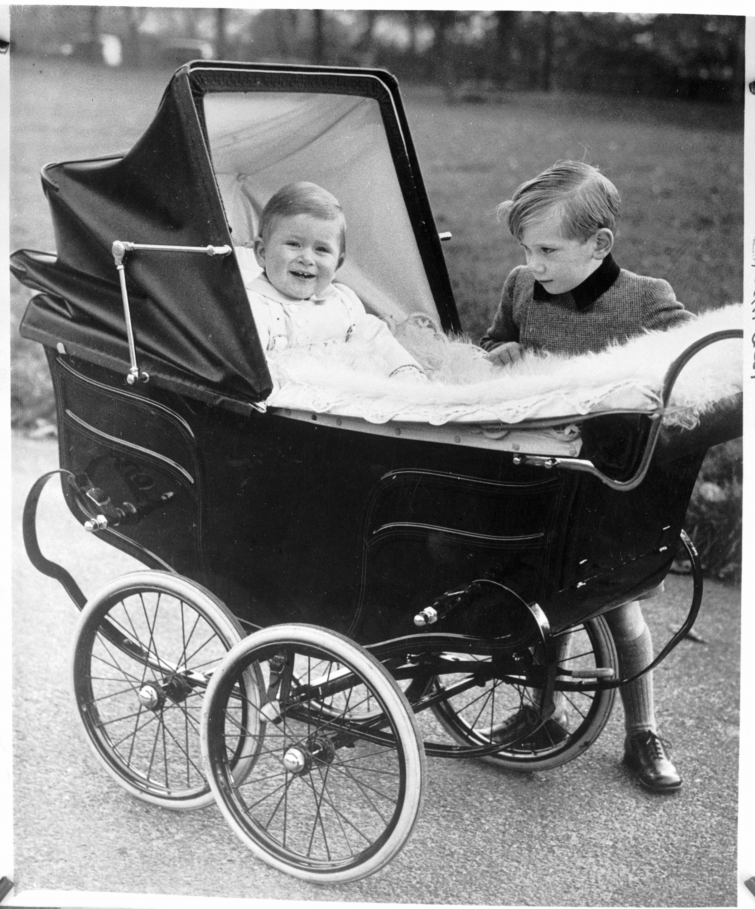 Prince Charles, son of Princess Elizabeth and the Duke of Edinburgh, beams from his pram as the photographer clicks the shutter during an outing in Green Park. The little boy studying the baby is Prince Richard, son of the Duke and Duchess of Gloucester an. (Photo by Bettmann/Corbis/Getty Images)