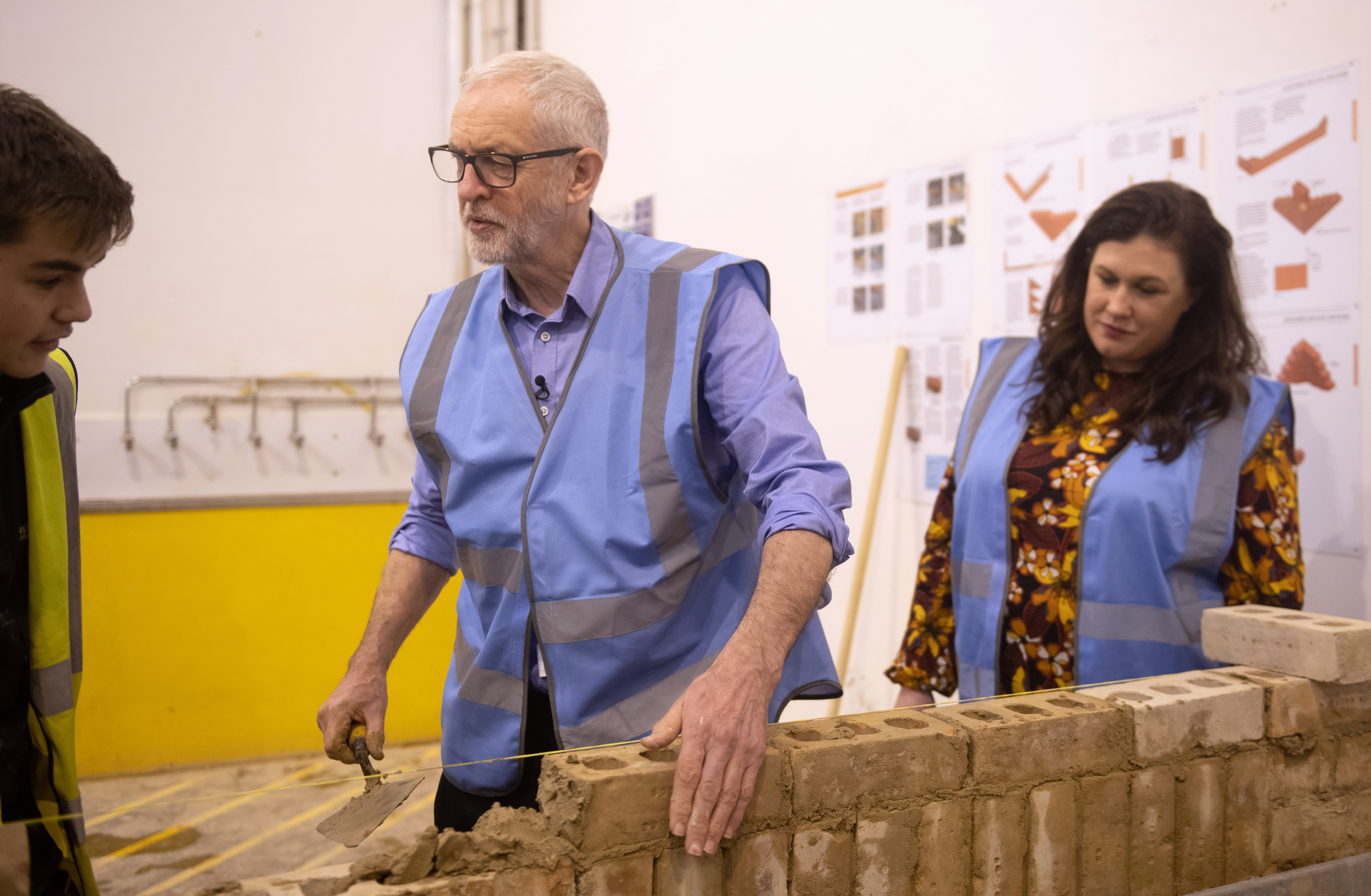 Labour Party leader Jeremy Corbyn tries his hand at bricklaying with apprentice Drew Wainwright (left) and parliamentary candidate for Ashfield Natalie Fleet (right) during a visit to the West Nottinghamshire College Construction Centre, in Ashfield, whilst on the General Election campaign trail.