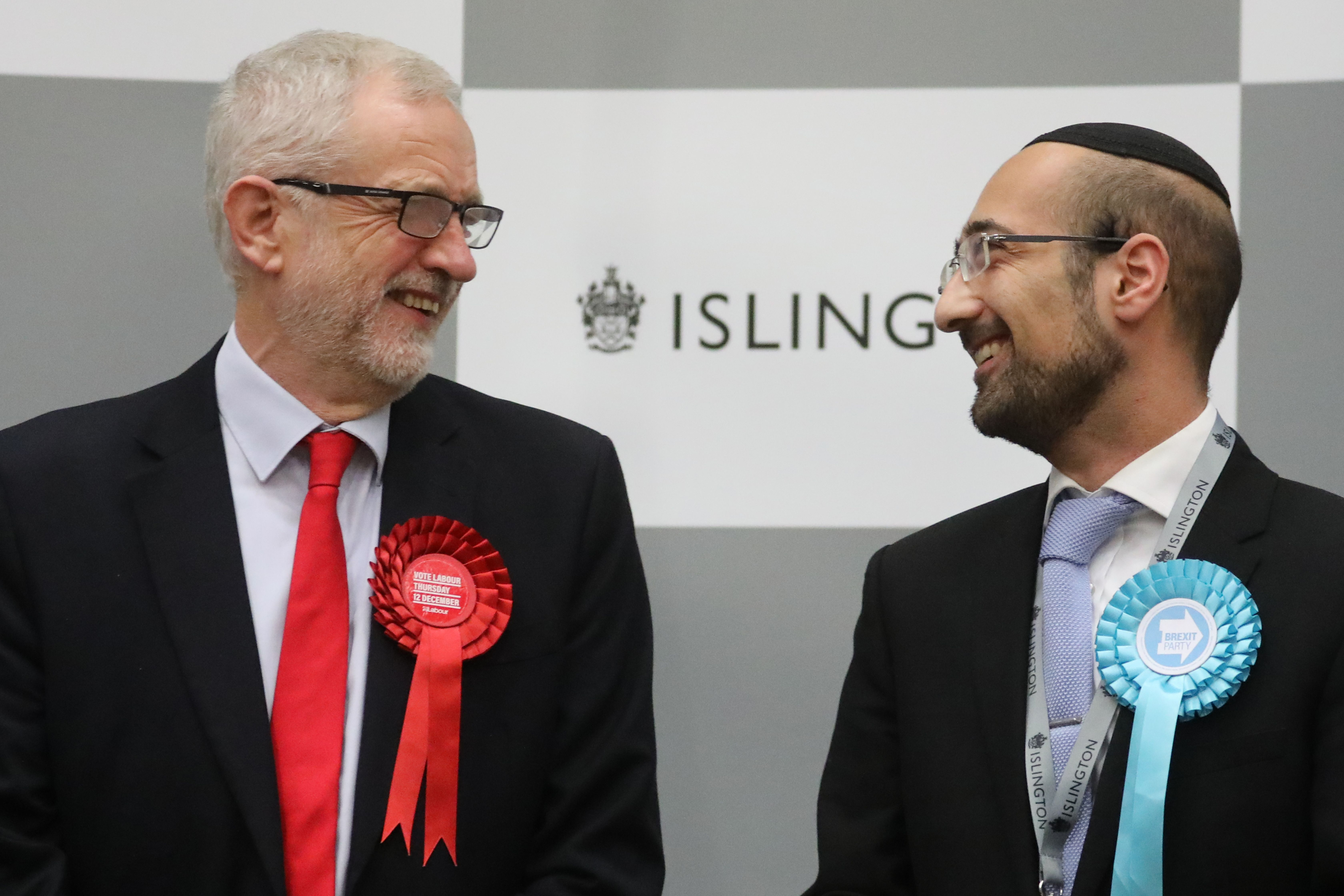 Britain's opposition Labour Party leader Jeremy Corbyn (L) exchanges a laugh with the Brexit Party candidate Yosef David  (R) as they stand on the stage to hear the results of the race to be MP for Islington North at the count centre in Islington, north London, on December 13, 2019 as part of the UK general election. (Photo by ISABEL INFANTES / AFP) (Photo by ISABEL INFANTES/AFP via Getty Images)