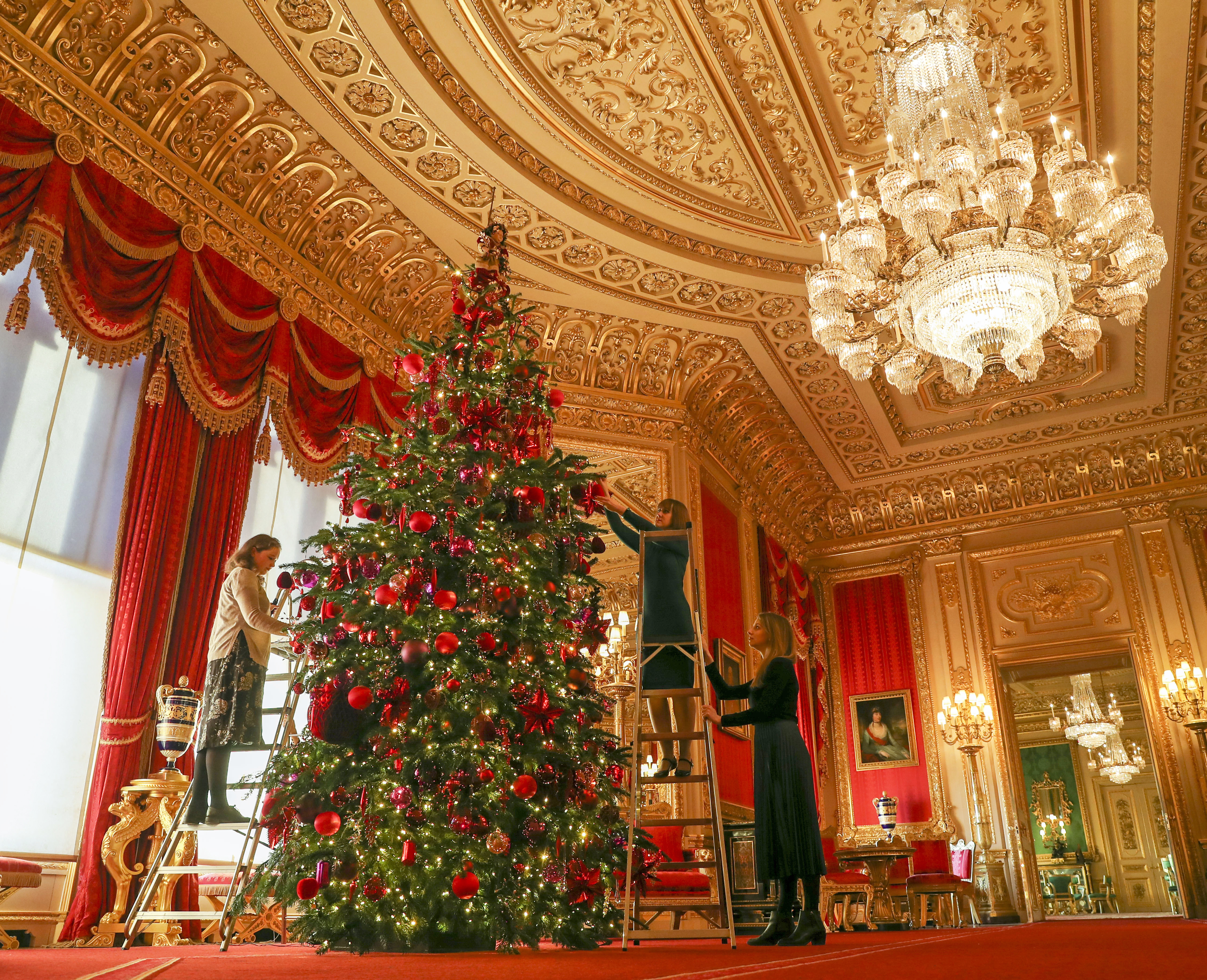 Royal Collection Trust members of staff put the finishing touches to a 15ft Christmas tree in the Crimson Drawing Room at Windsor Castle, Berkshire. (Photo by Steve Parsons/PA Images via Getty Images)