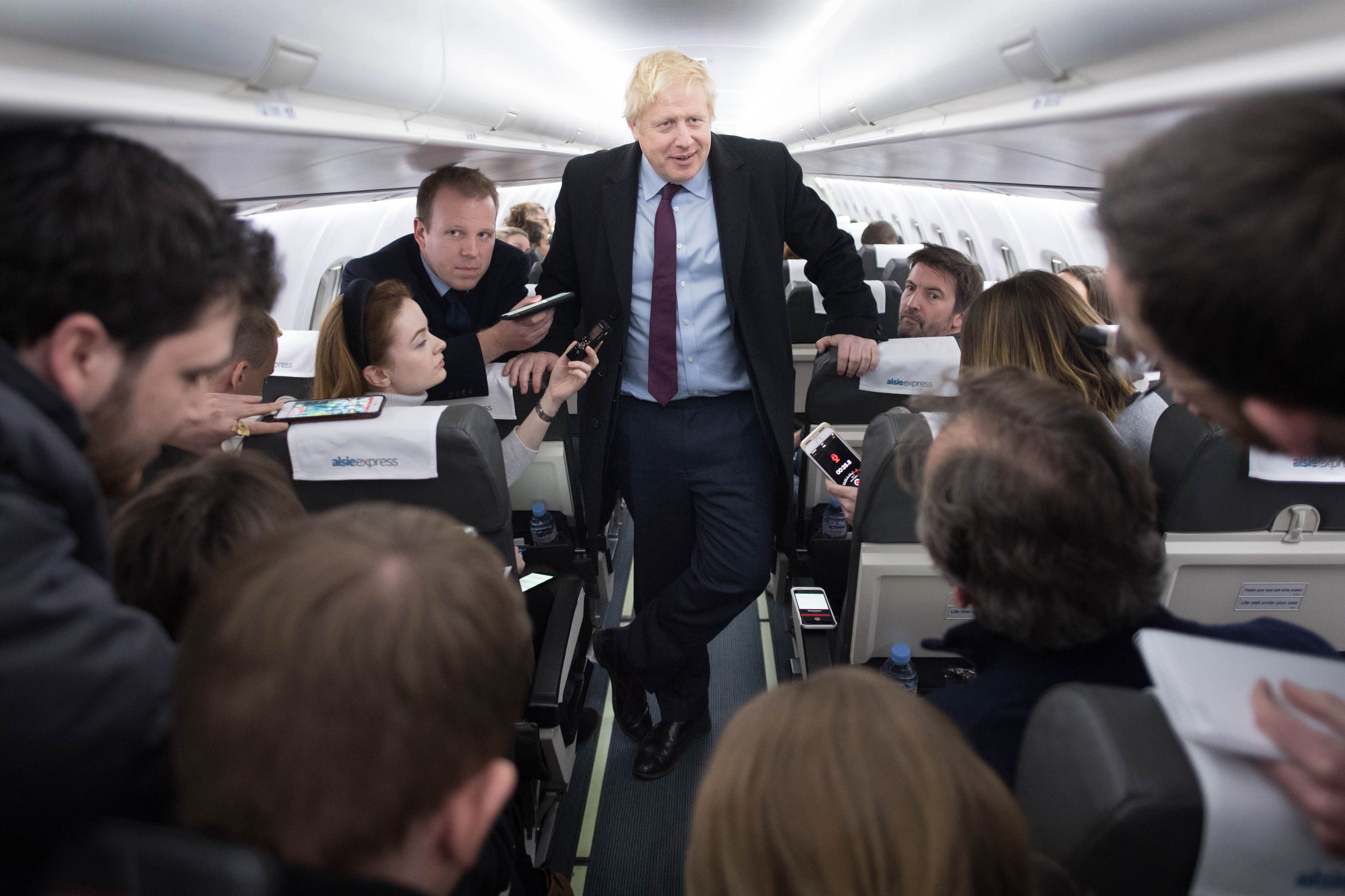 Prime Minister Boris Johnson speaks to the press on board his campaign plane whilst travelling to Birmingham after a day of visits in Grimsby and the north east. PA Photo. Picture date: Monday December 9, 2019. See PA story POLITICS Election. Photo credit should read: Stefan Rousseau/PA Wire