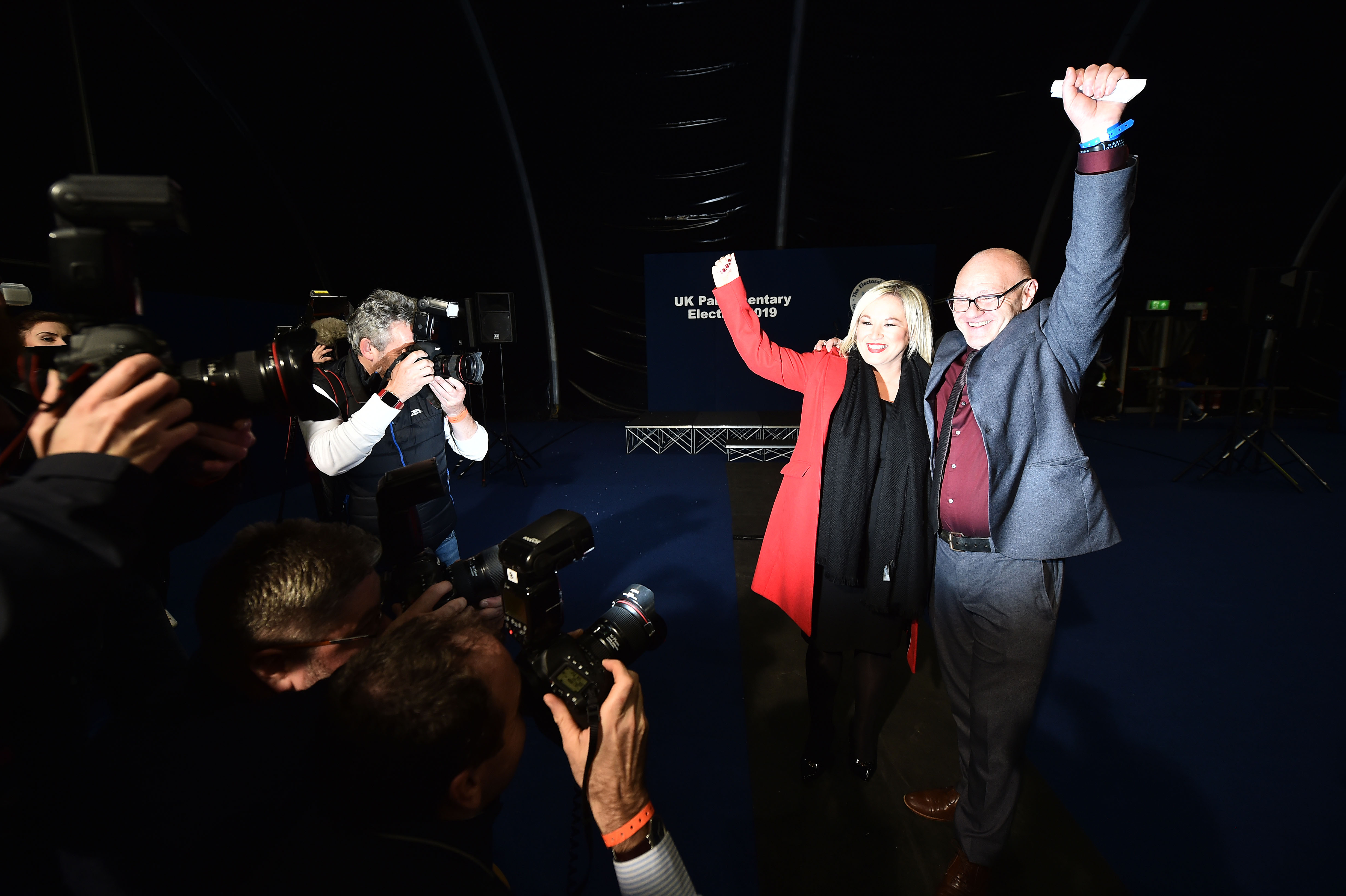BELFAST, NORTHERN IRELAND - DECEMBER 13:  Sinn Fein candidate Paul Maskey celebrates his victory in the west Belfast constituency alongside Sinn Fein northern leader Michelle ONeill in the Belfast count centre at the Titanic Exhibition centre on December 13, 2019 in Belfast, United Kingdom. The current Conservative Prime Minister Boris Johnson called the first UK winter election for nearly a century in an attempt to gain a working majority to break the parliamentary deadlock over Brexit. The election results from across the country are being counted and an overall result is expected in the early hours of Friday morning. (Photo by Charles McQuillan/Getty Images)
