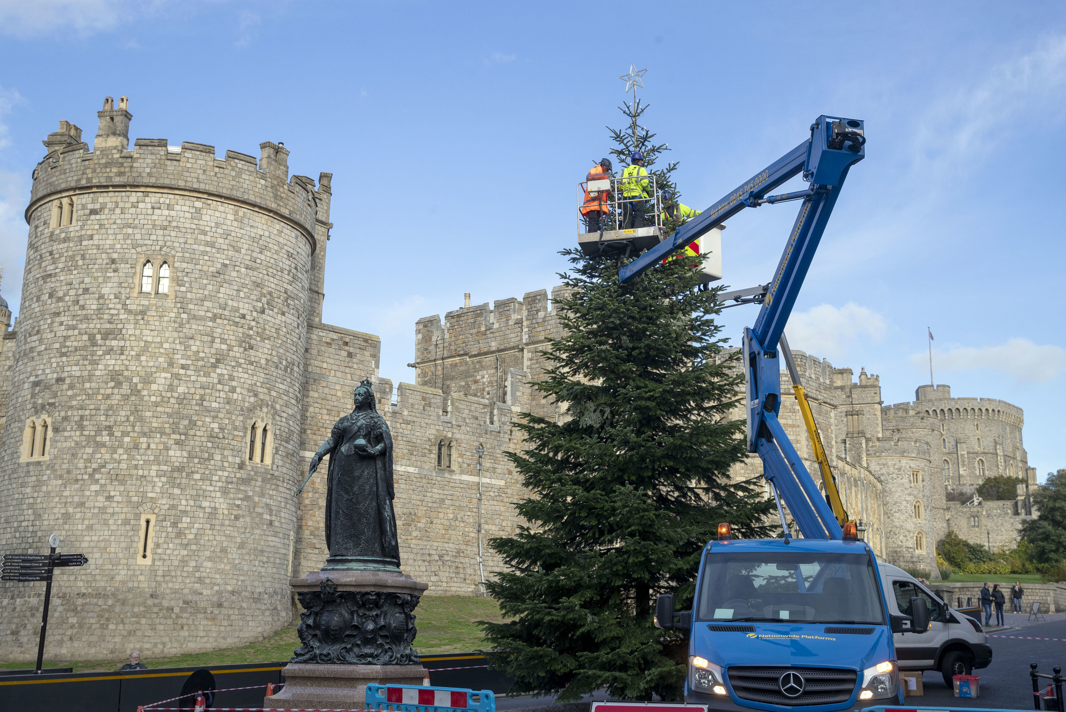 Lights are installed onto the Christmas tree outside Windsor Castle, Berkshire, ahead of the Christmas Lights Switch on and Lantern Procession on November 17, by Staff from Lamps and Tubes illuminations Ltd working for the Royal Borough of Windsor and Maidenhead. (Photo by Steve Parsons/PA Images via Getty Images)