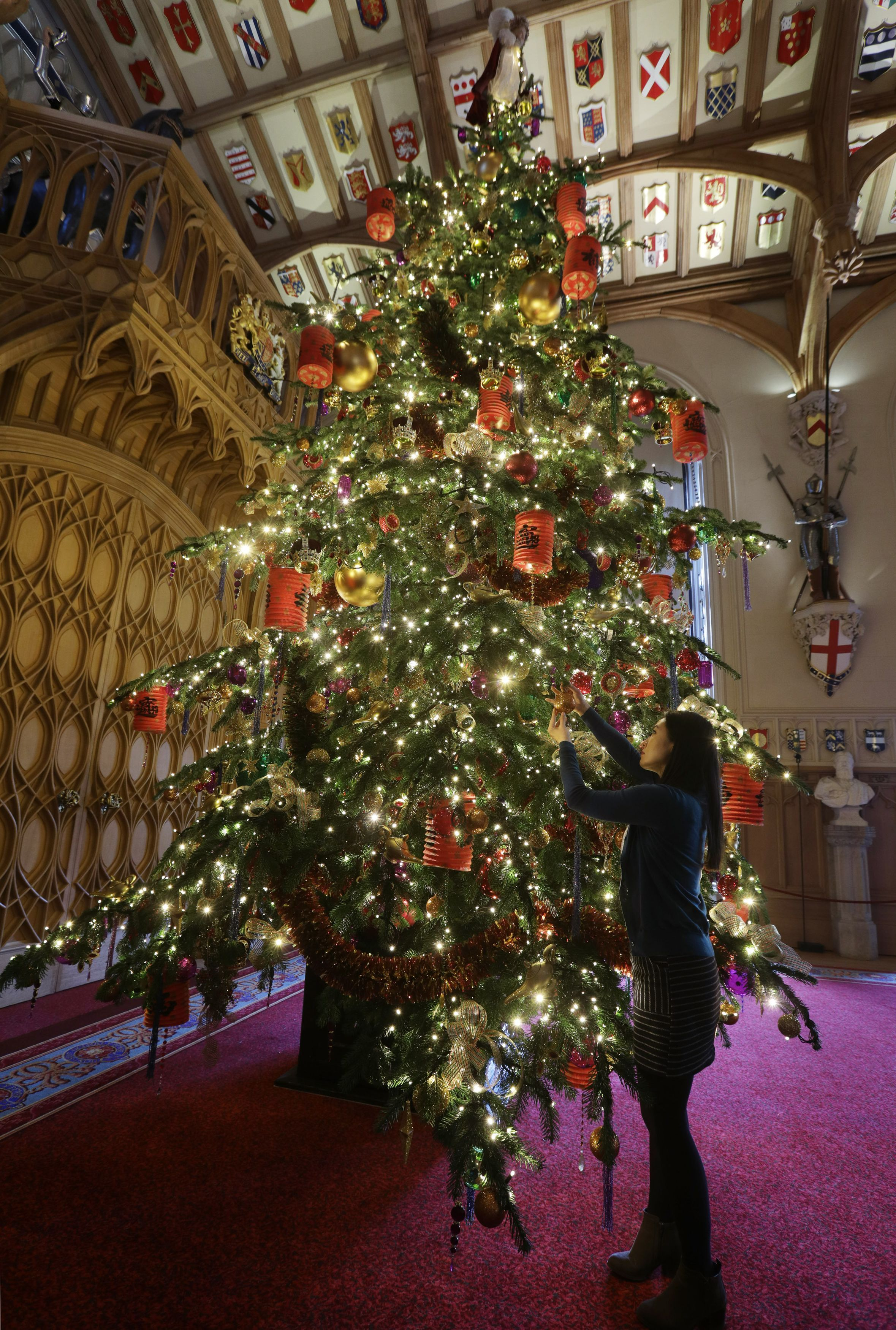 A Royal Collection Trust staff member puts the finishing touches to a 20ft Nordmann fir tree in St George's Hall, as part of Christmas decorations being put up at Windsor Castle, Berkshire. (Photo by Yui Mok/PA Images via Getty Images)