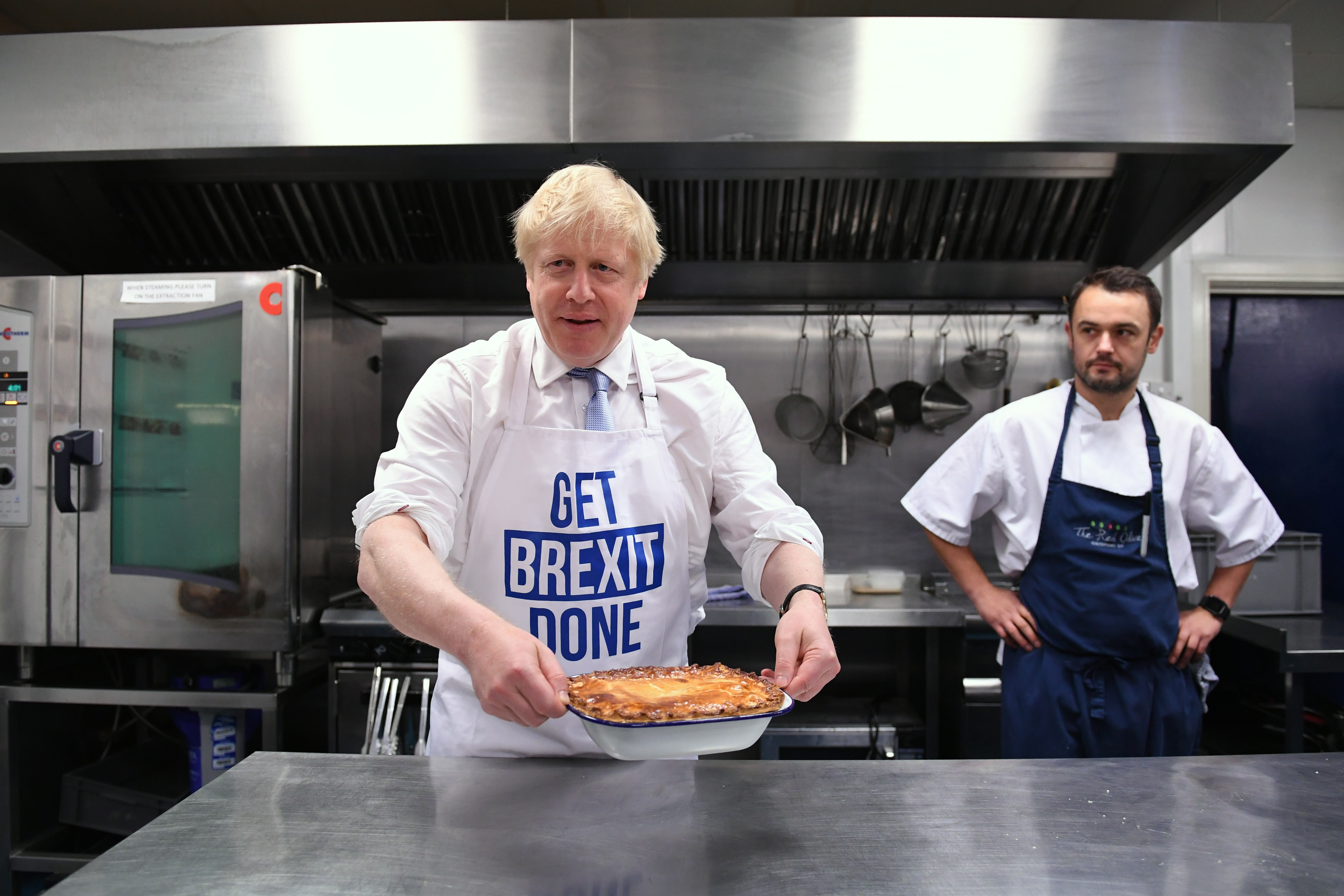 Prime Minister Boris Johnson holds a freshly bakes pie during a visit to the Red Olive in Derby, while on the General Election campaign trail.